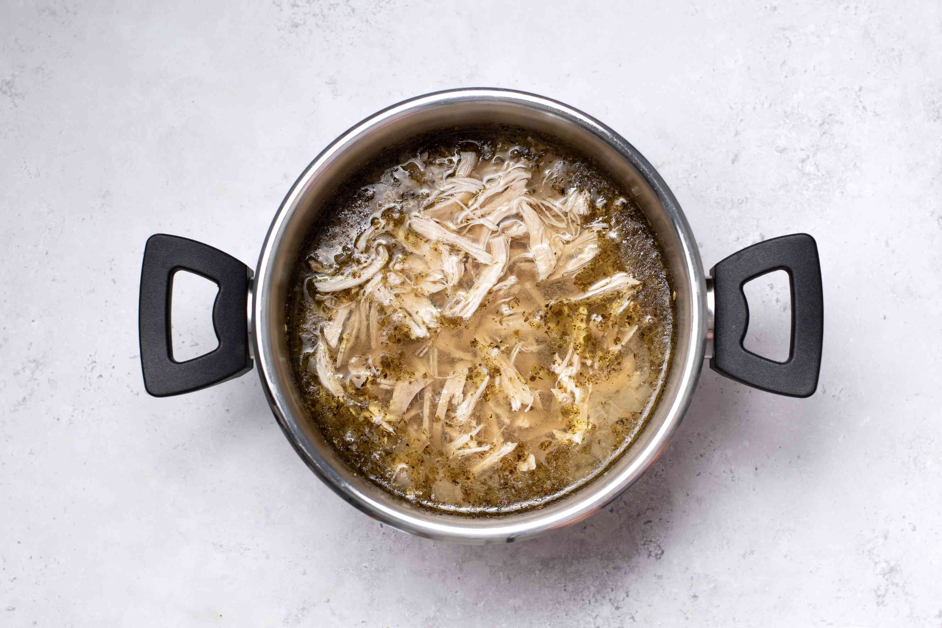 shredded chicken in a pot with soup