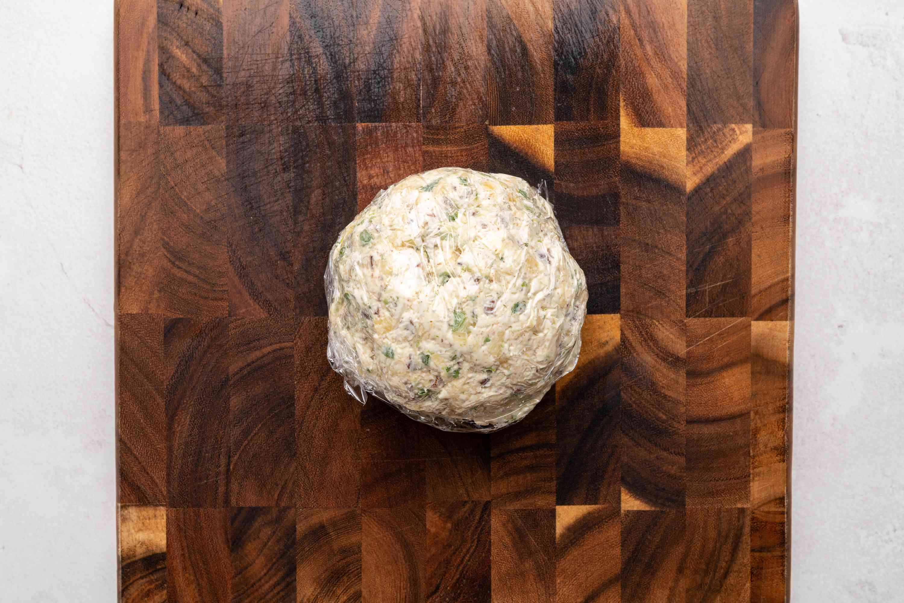cheese ball wrapped in plastic wrap