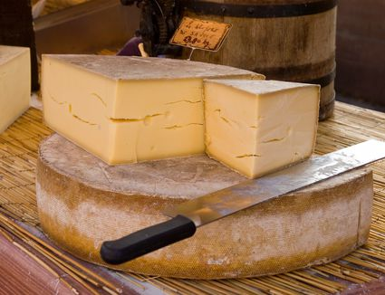 Wheel of cut gruyere cheese on a table with a knife