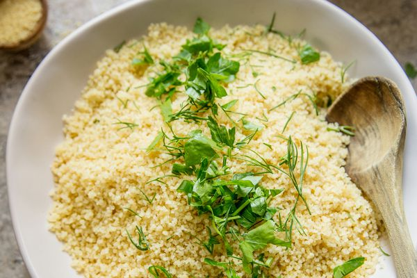 Couscous in a bowl garnished with fresh herbs