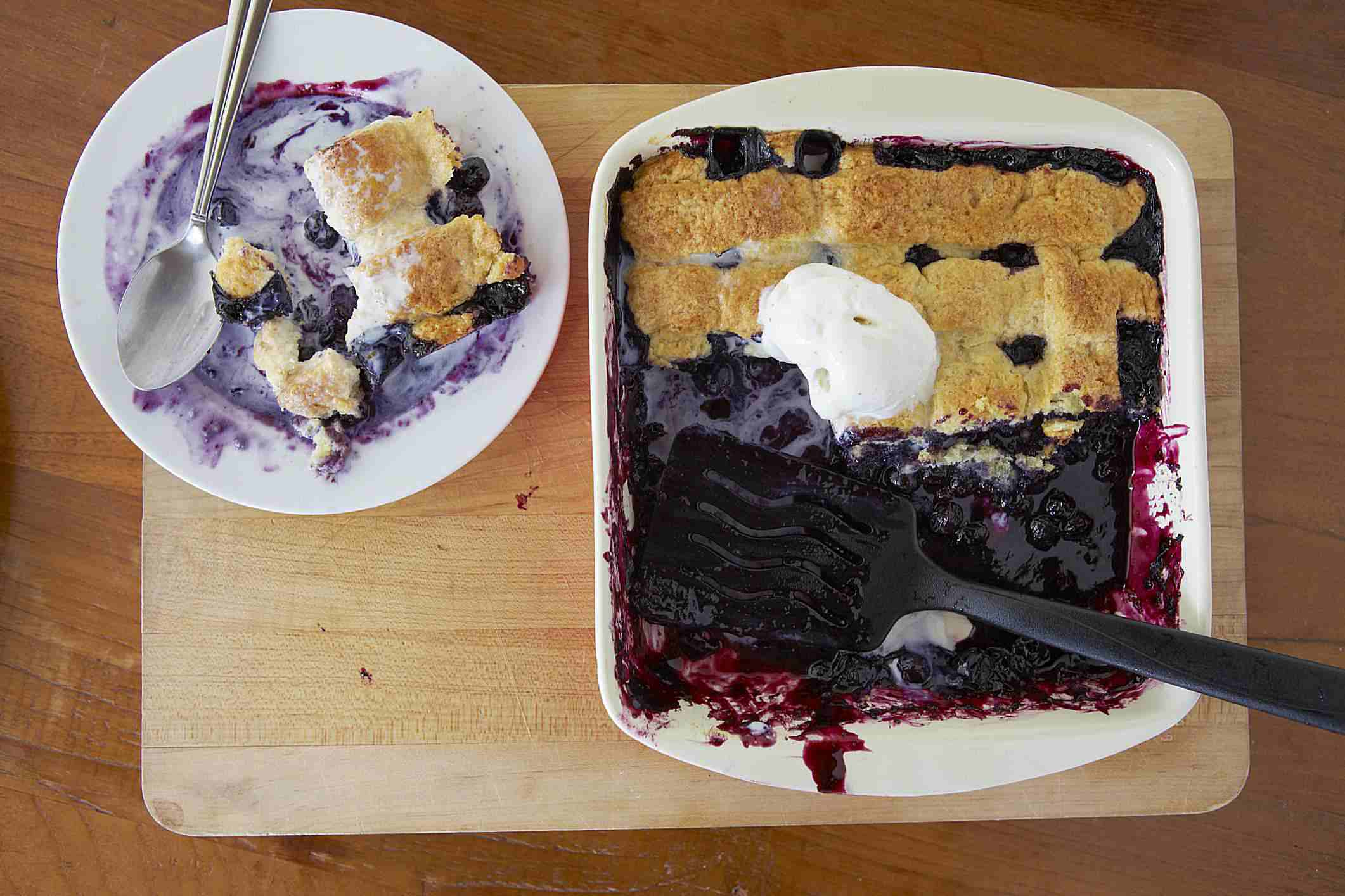 Blueberry cobbler being served from a baking dish
