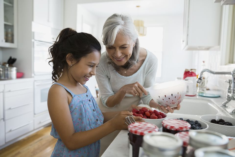 Grandmother and granddaughter making fresh jam in kitchen