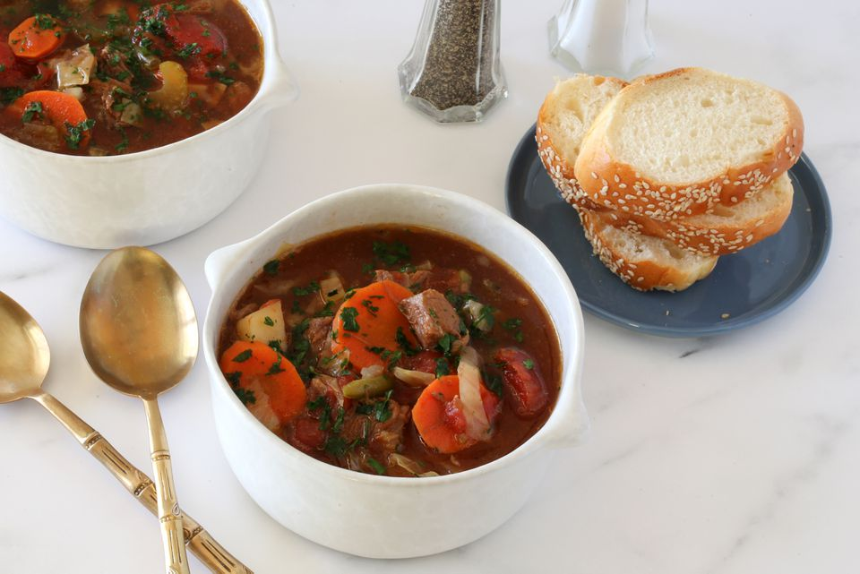 Vegetable beef soup with sliced bread.