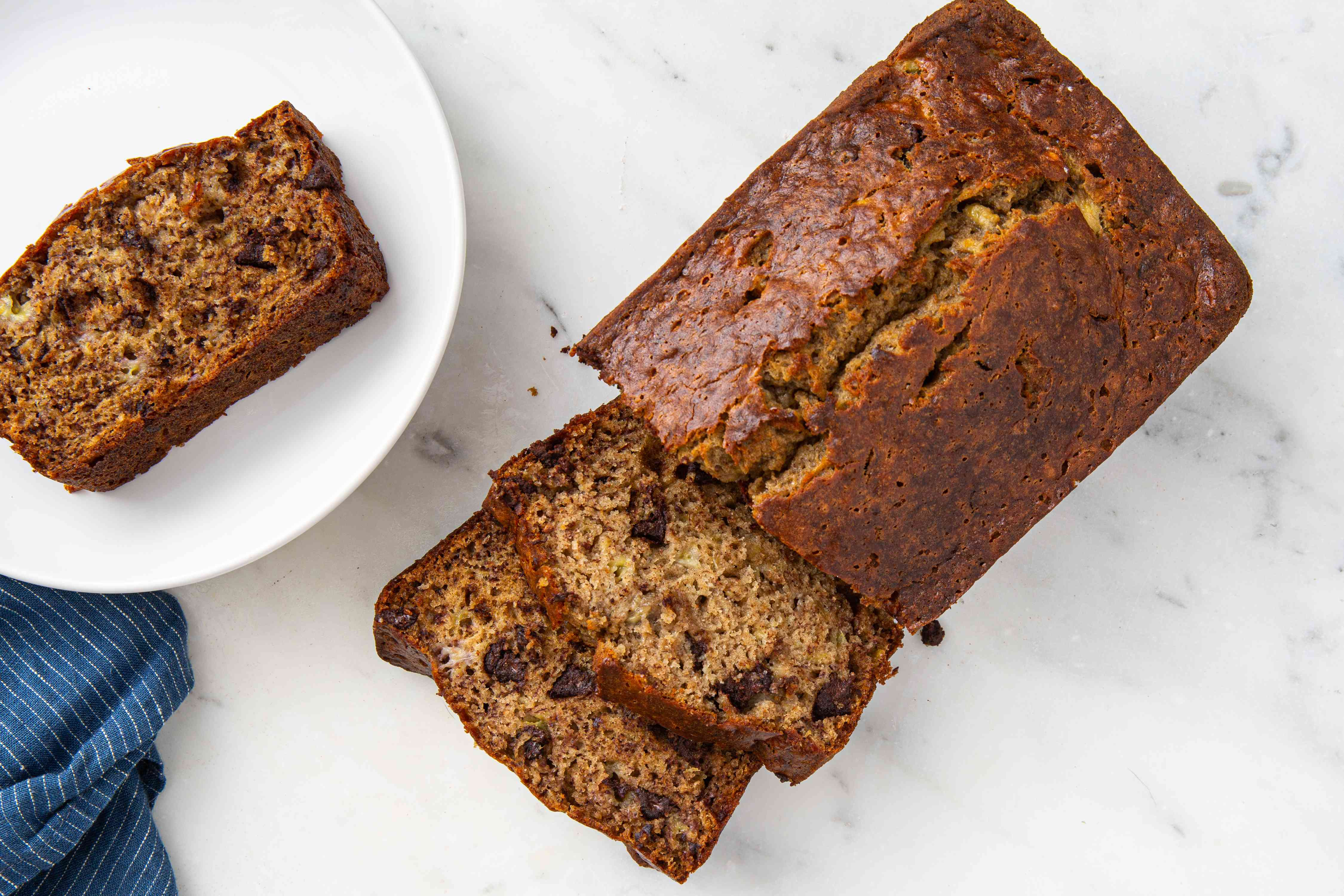 Moist Banana Bread With Coconut Oil, loaf of banana bread on a white marble table