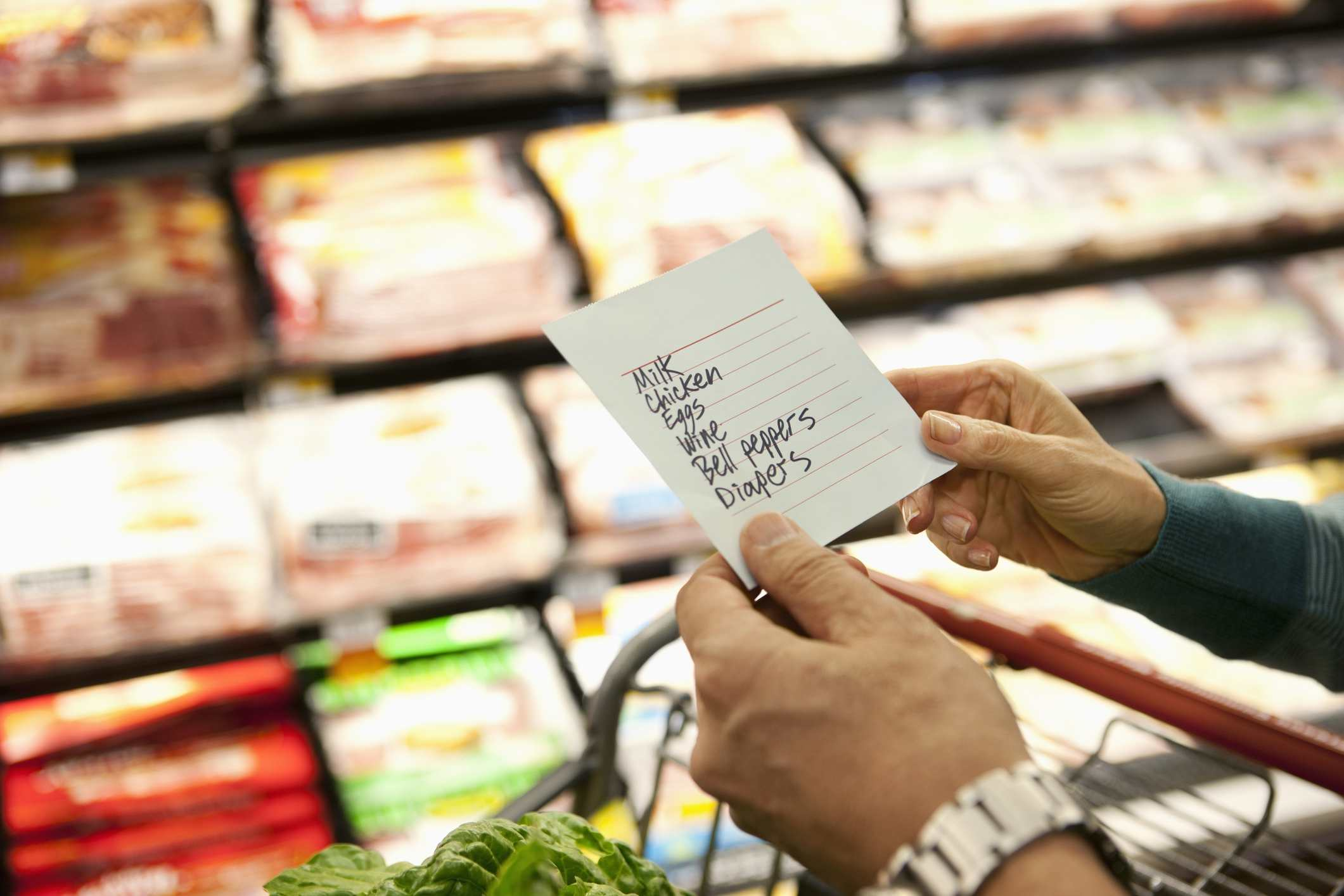 Older woman reading grocery list in supermarket