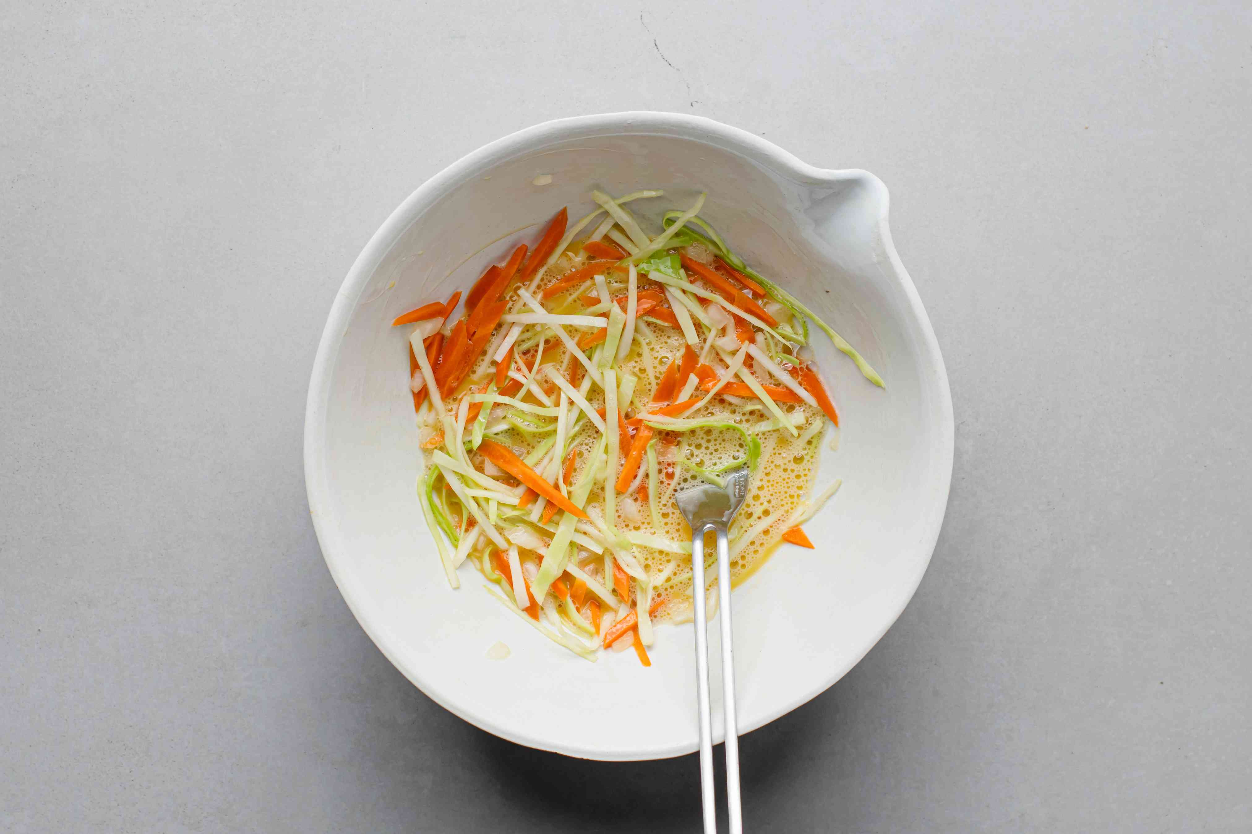 eggs with carrots, cabbage and onions in a bowl