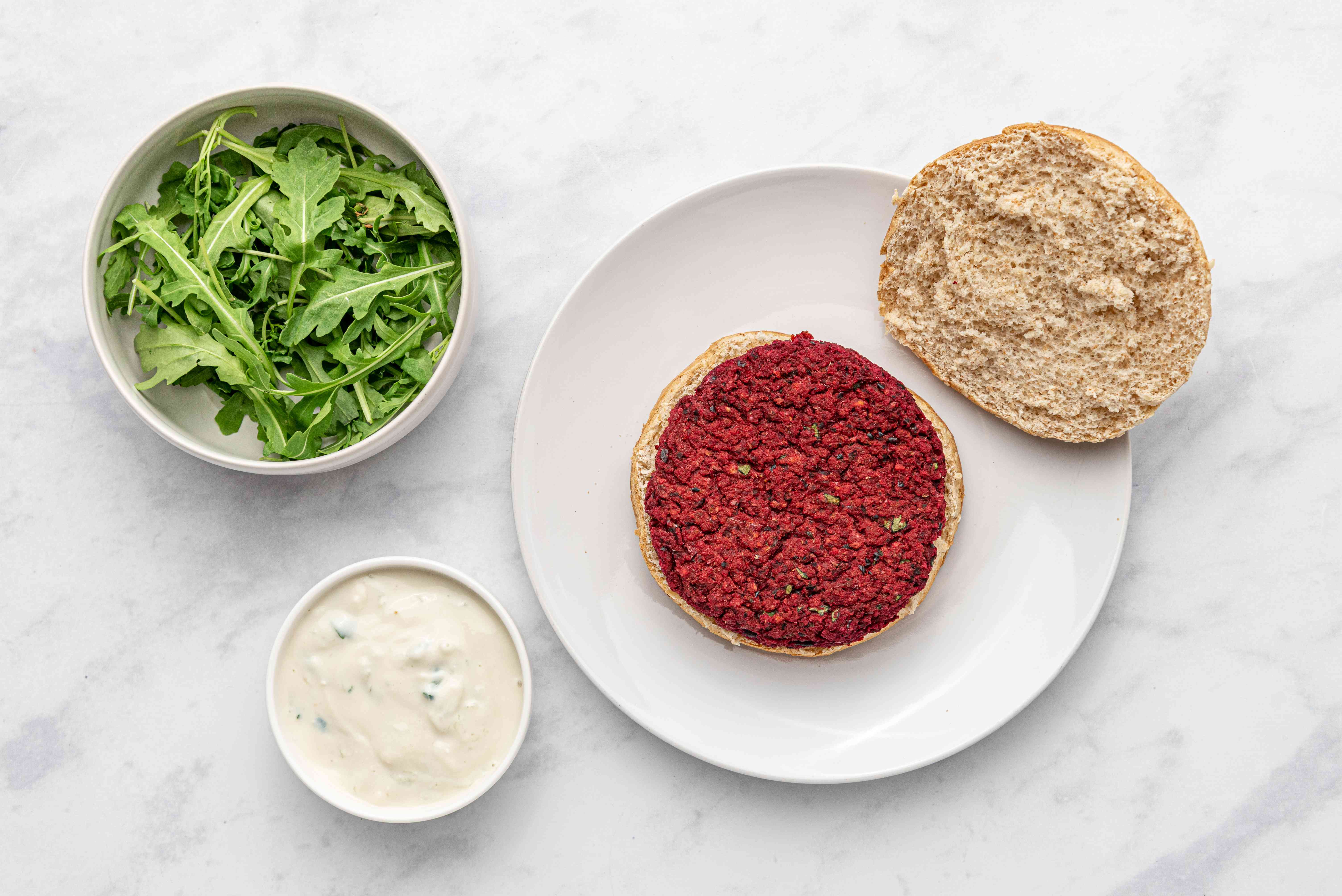Beet Burger on a plate, sauce and arugula on the side
