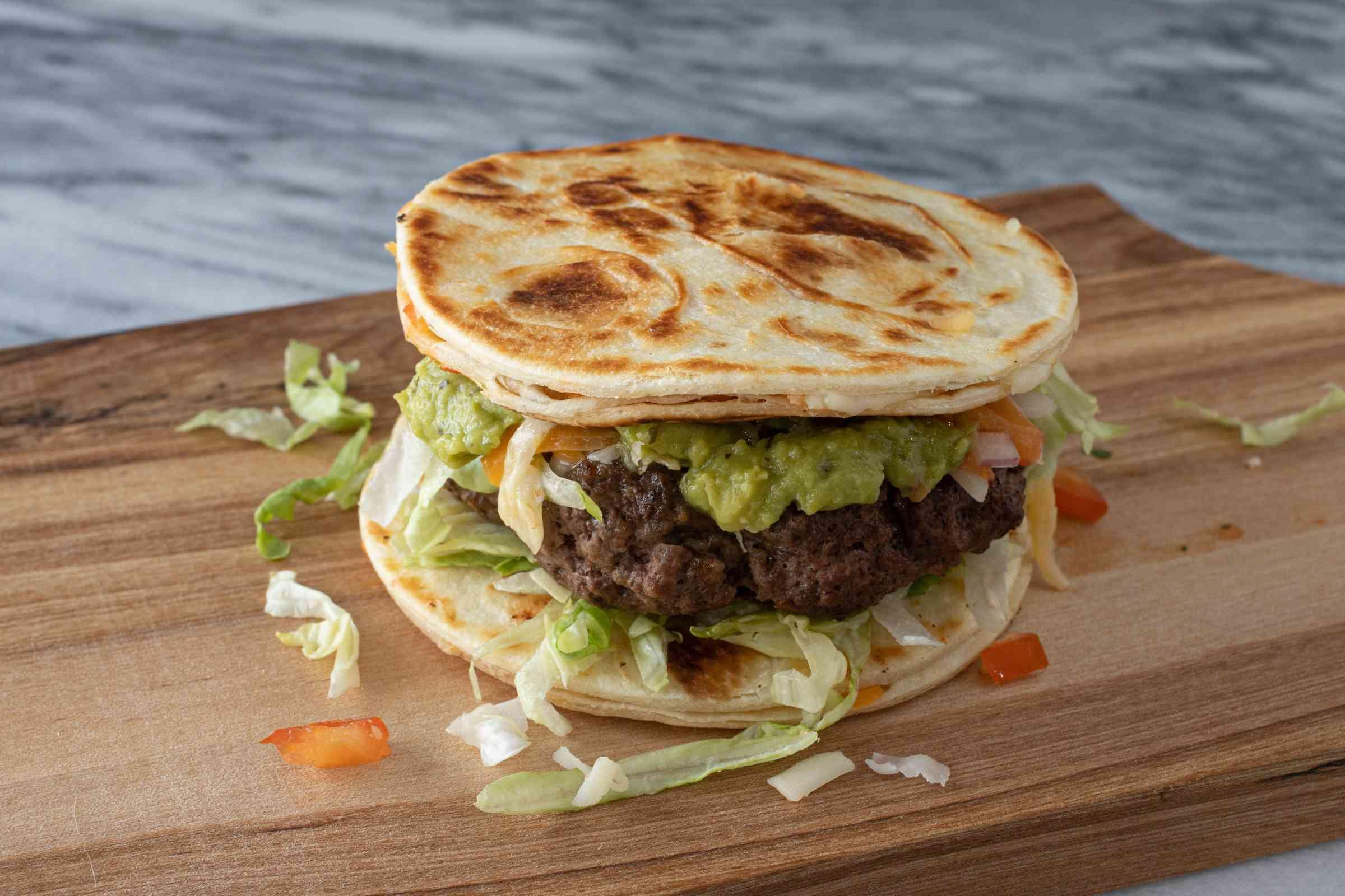 Quesadilla burger assembled on cutting board.