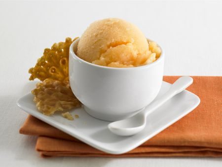 Orange Sherbet In A Cup With Cookie On The Side