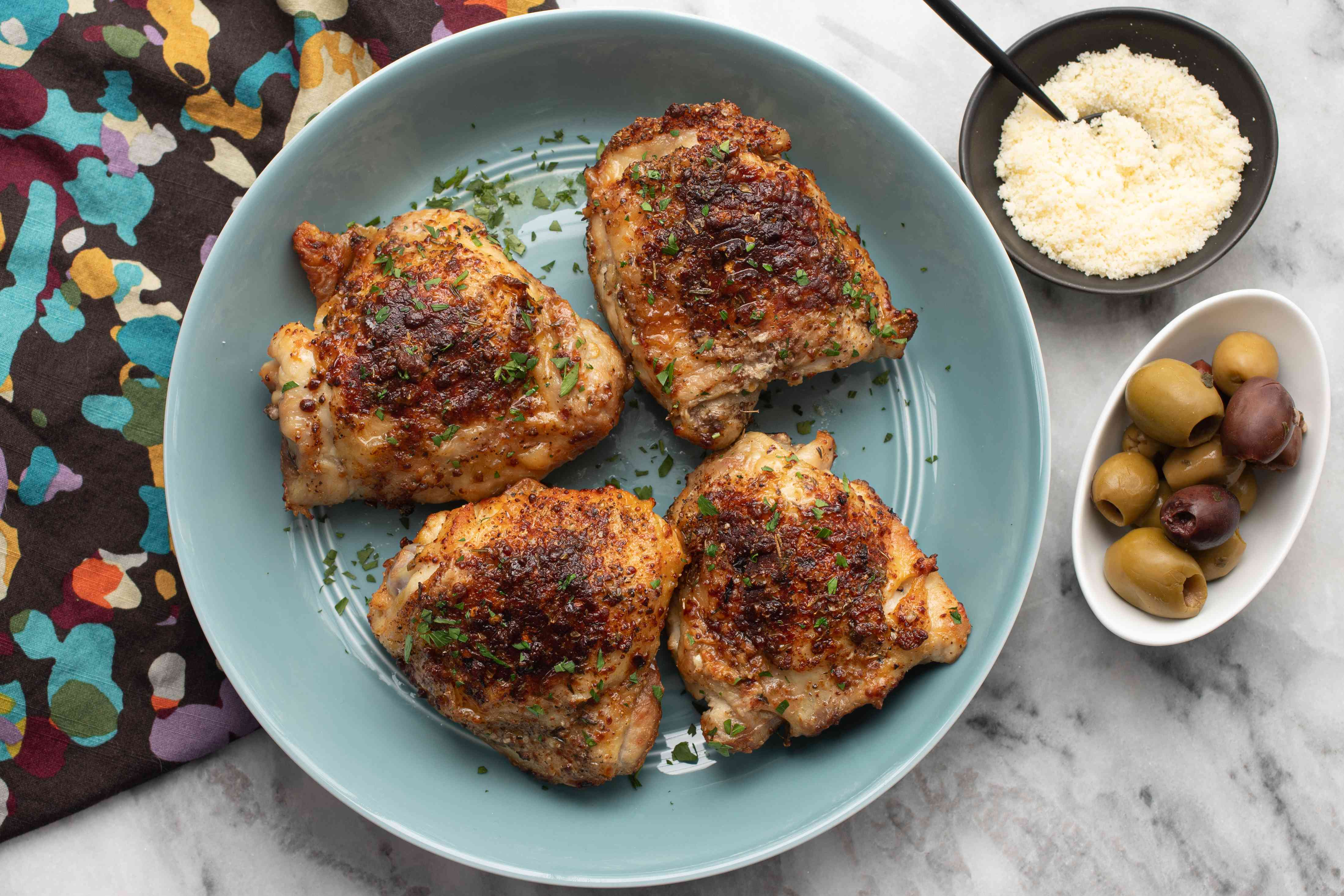 chicken thighs on a plate with parmesan cheese on the side