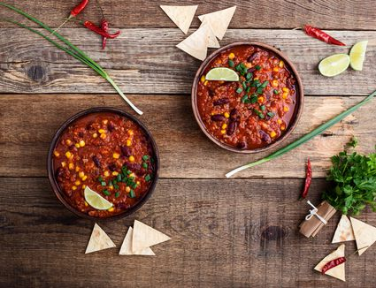 Chili in bowls with limes and tortilla chips