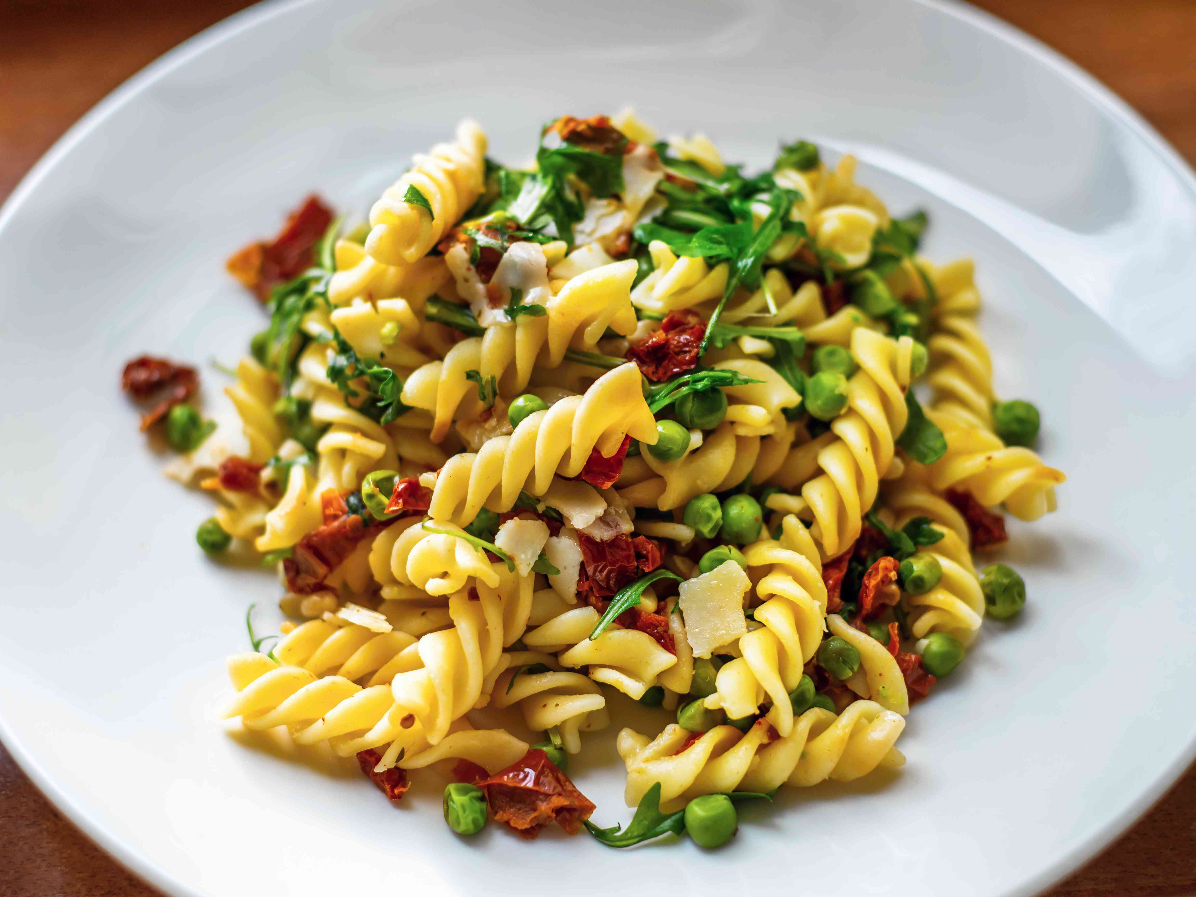 Fusilli pasta with vegetable on plate.
