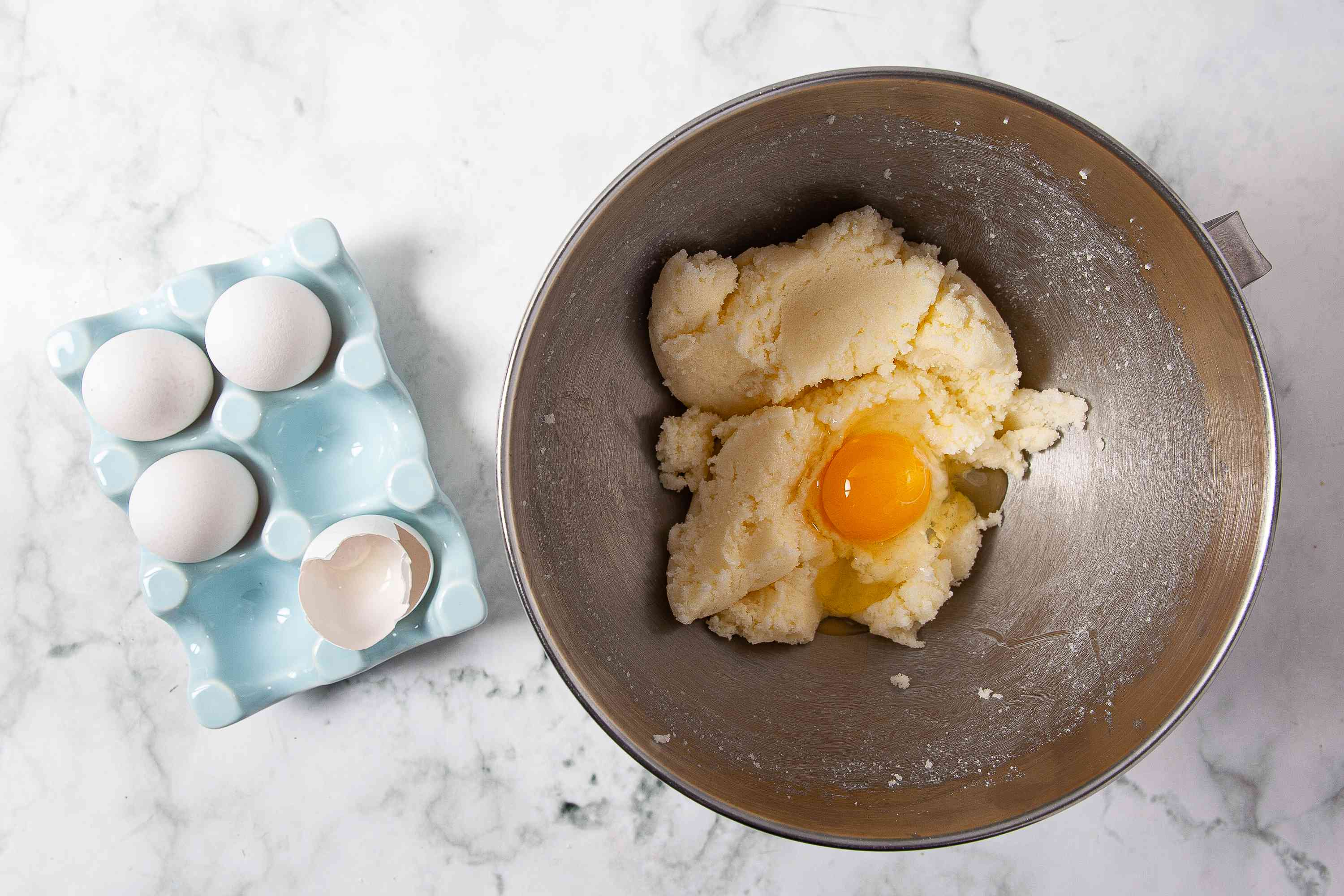 Adding eggs to the creamed butter and sugar