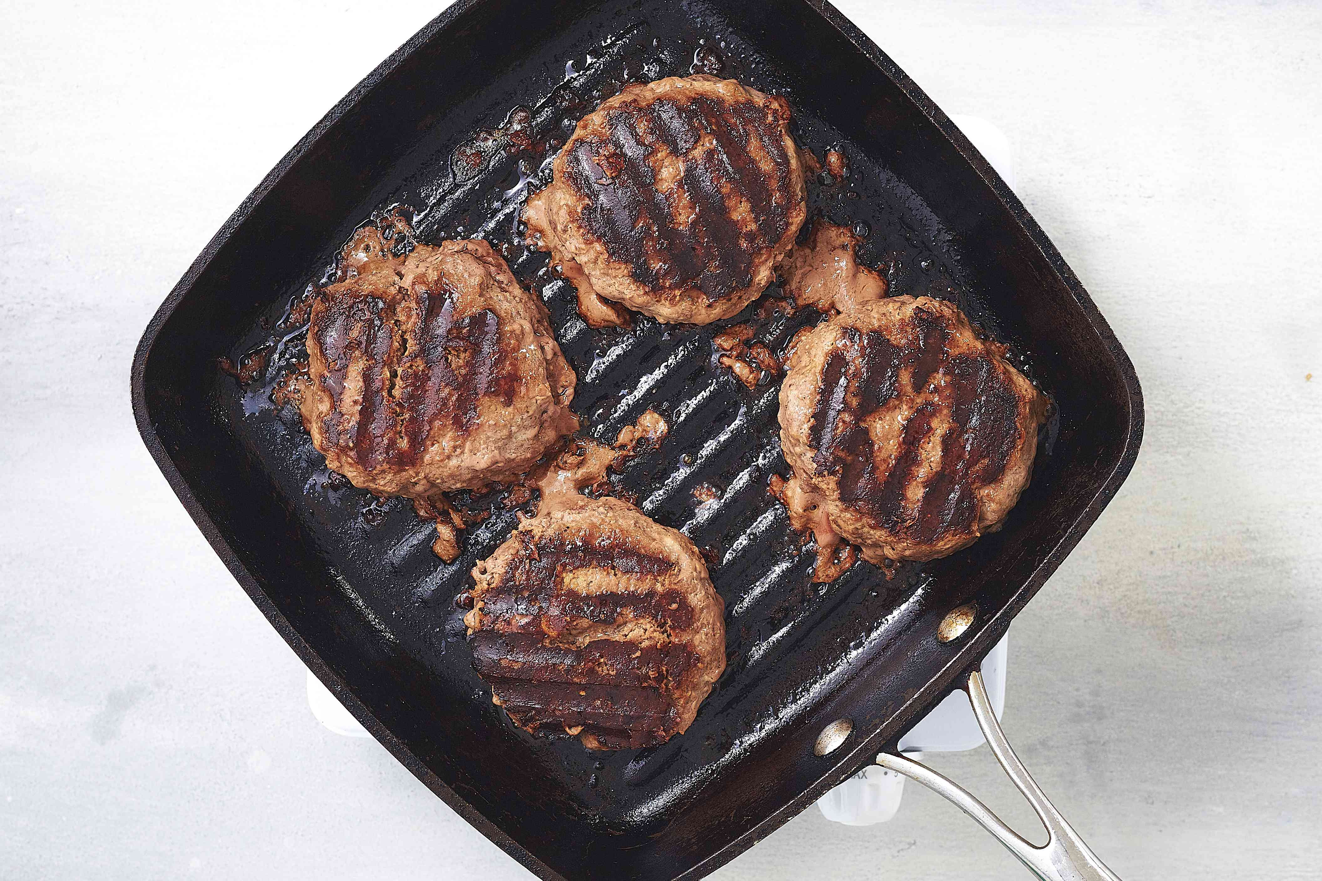 burger patties cooking on a grill pan