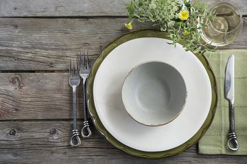 Place setting and wine on rustic wood table