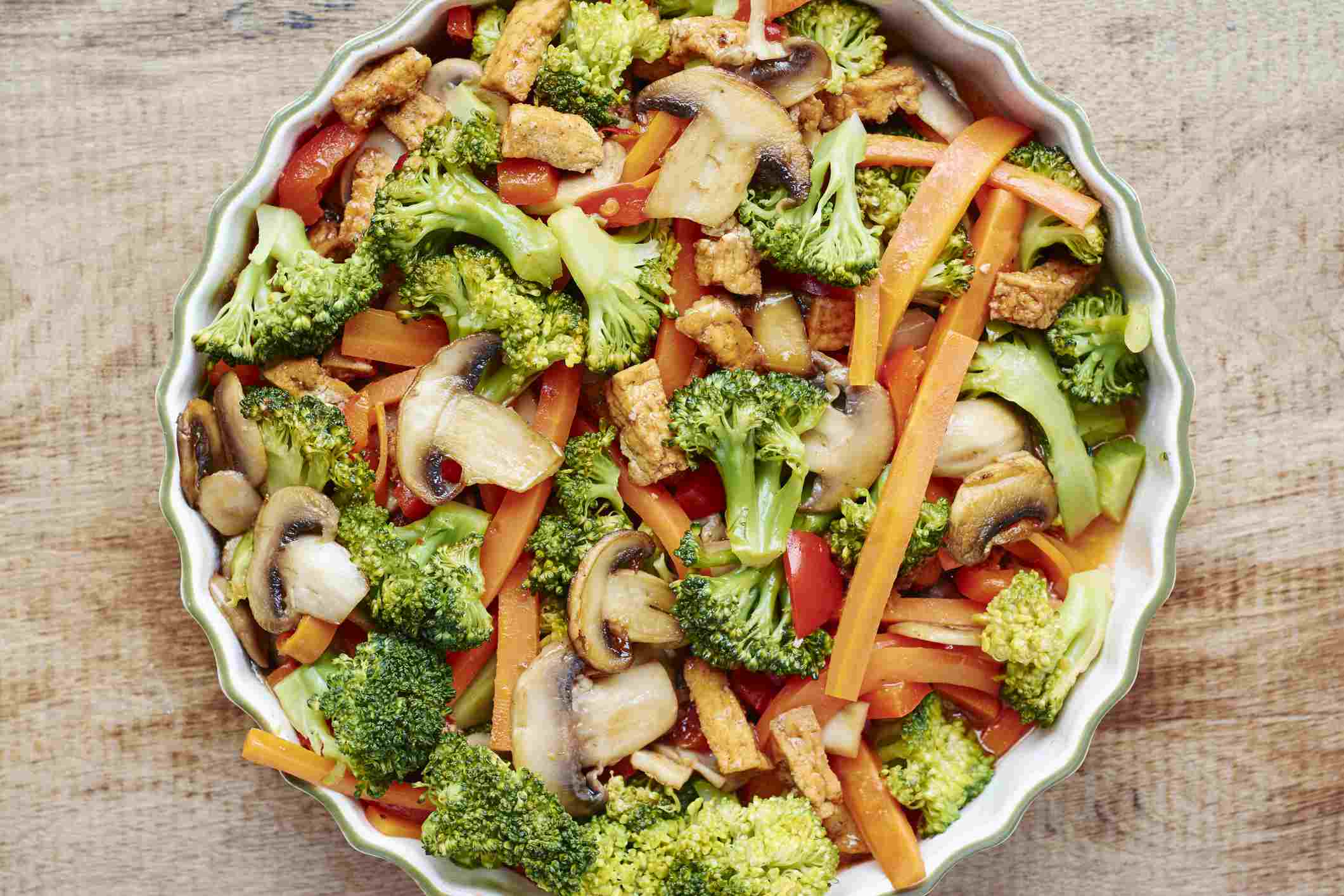 Broccoli, carrot, mushroom stir-fry with tofu in a serving bowl