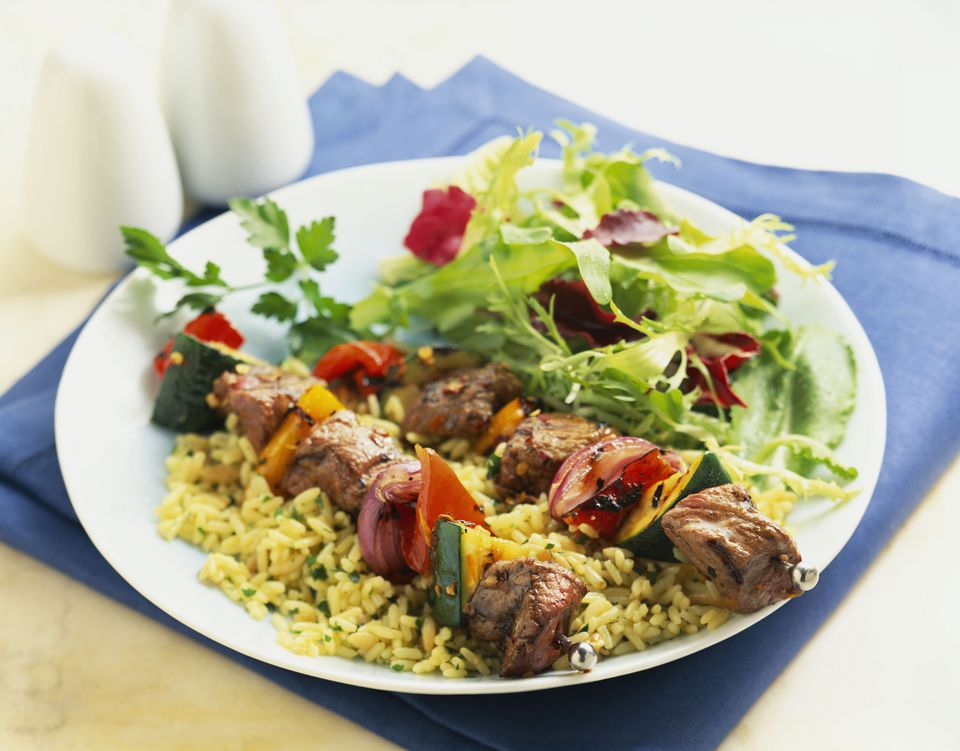 kabobs over rice with salad