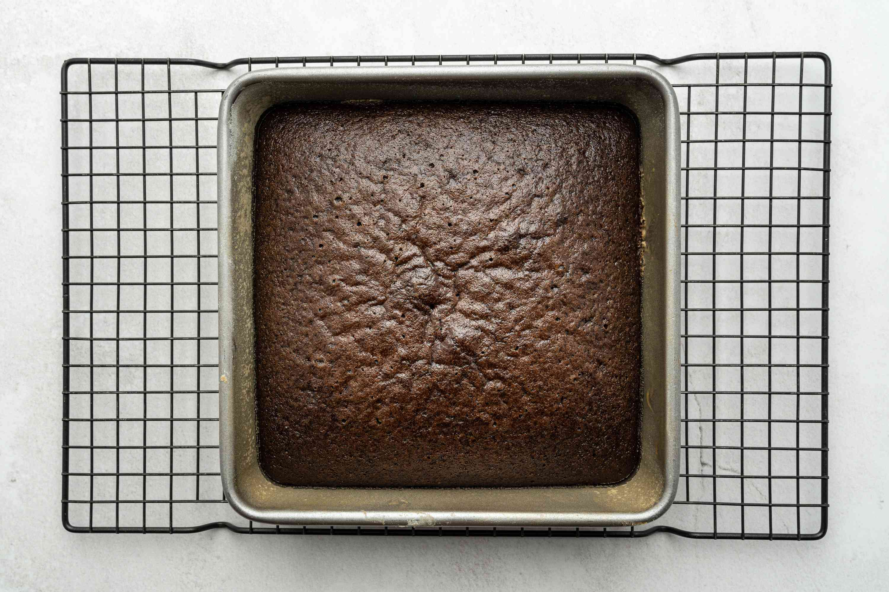 baked wacky cake in a baking pan on a cooling rack