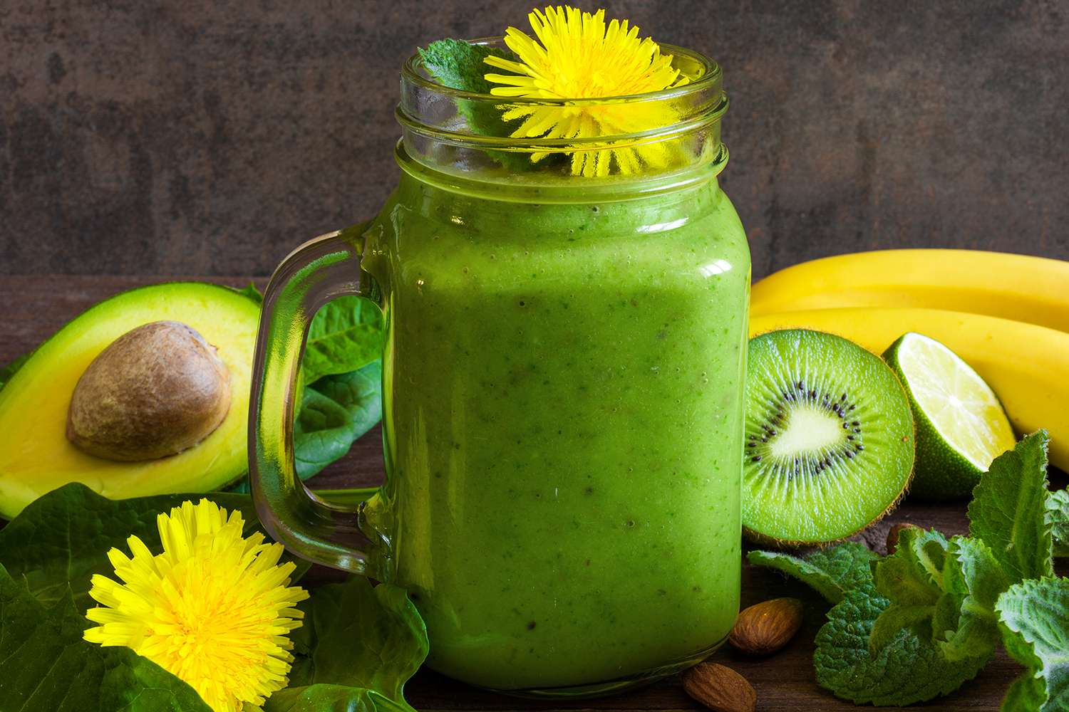 Green healthy smoothie in glass jar with avocado, banana, kiwi, spinach, mint, almonds and dandelion on rustic wooden background