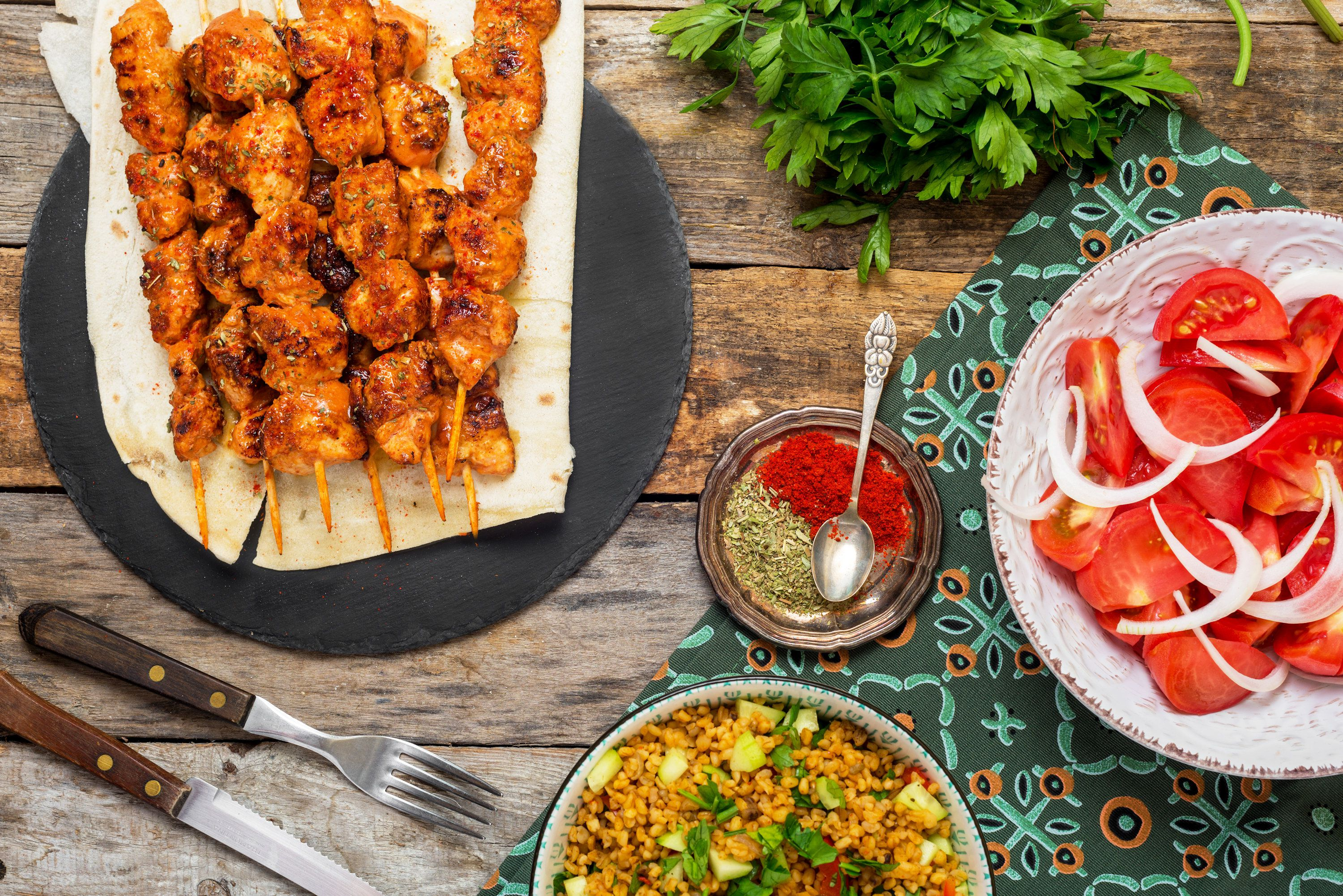 Turkish chicken kebab with sides and condiments