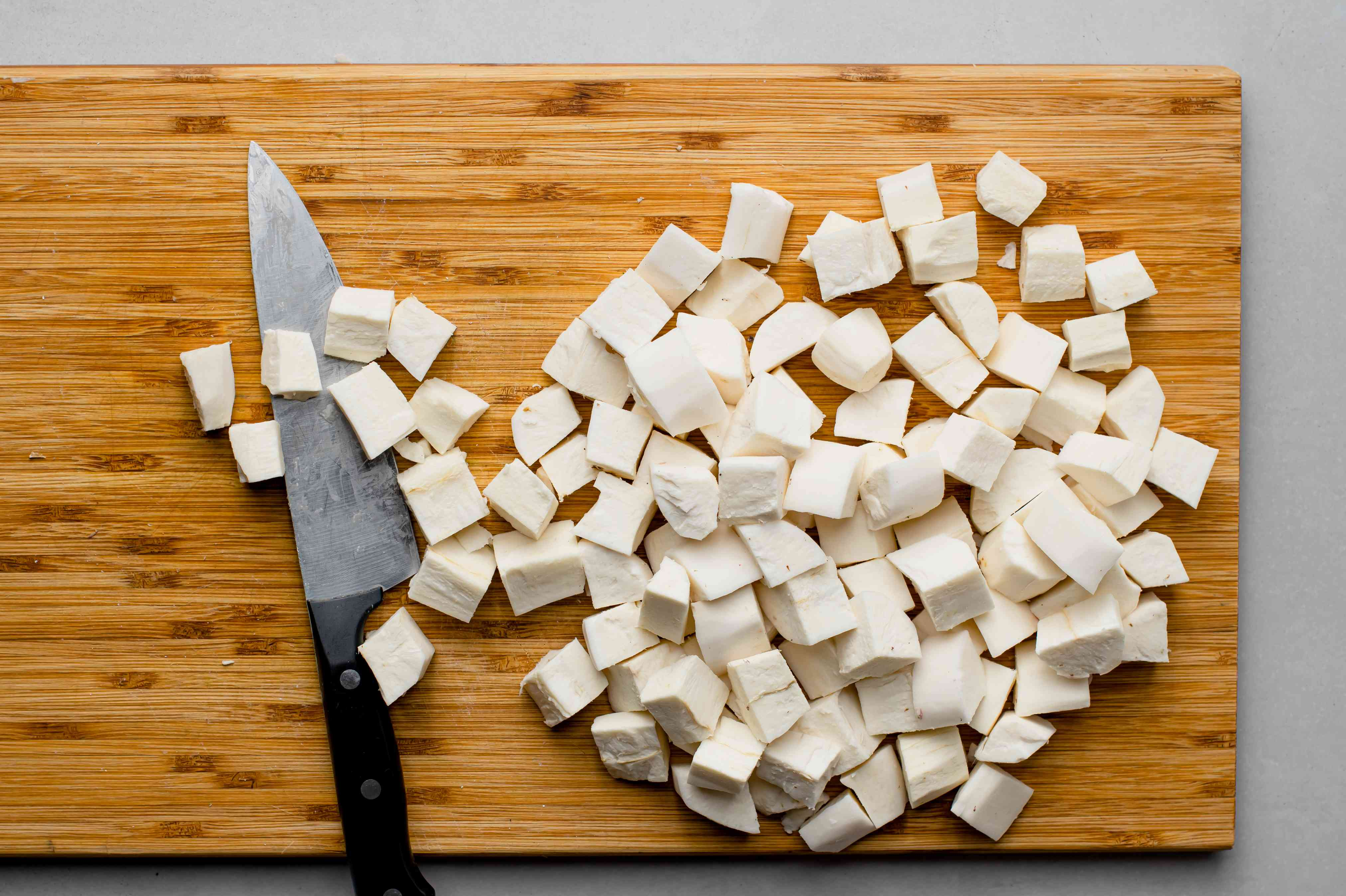 Peeled and cubed yuca on a cutting board with a knife