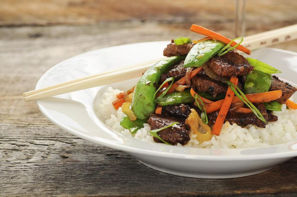 Beef and vegetables stir-fry over white rice with chopsticks