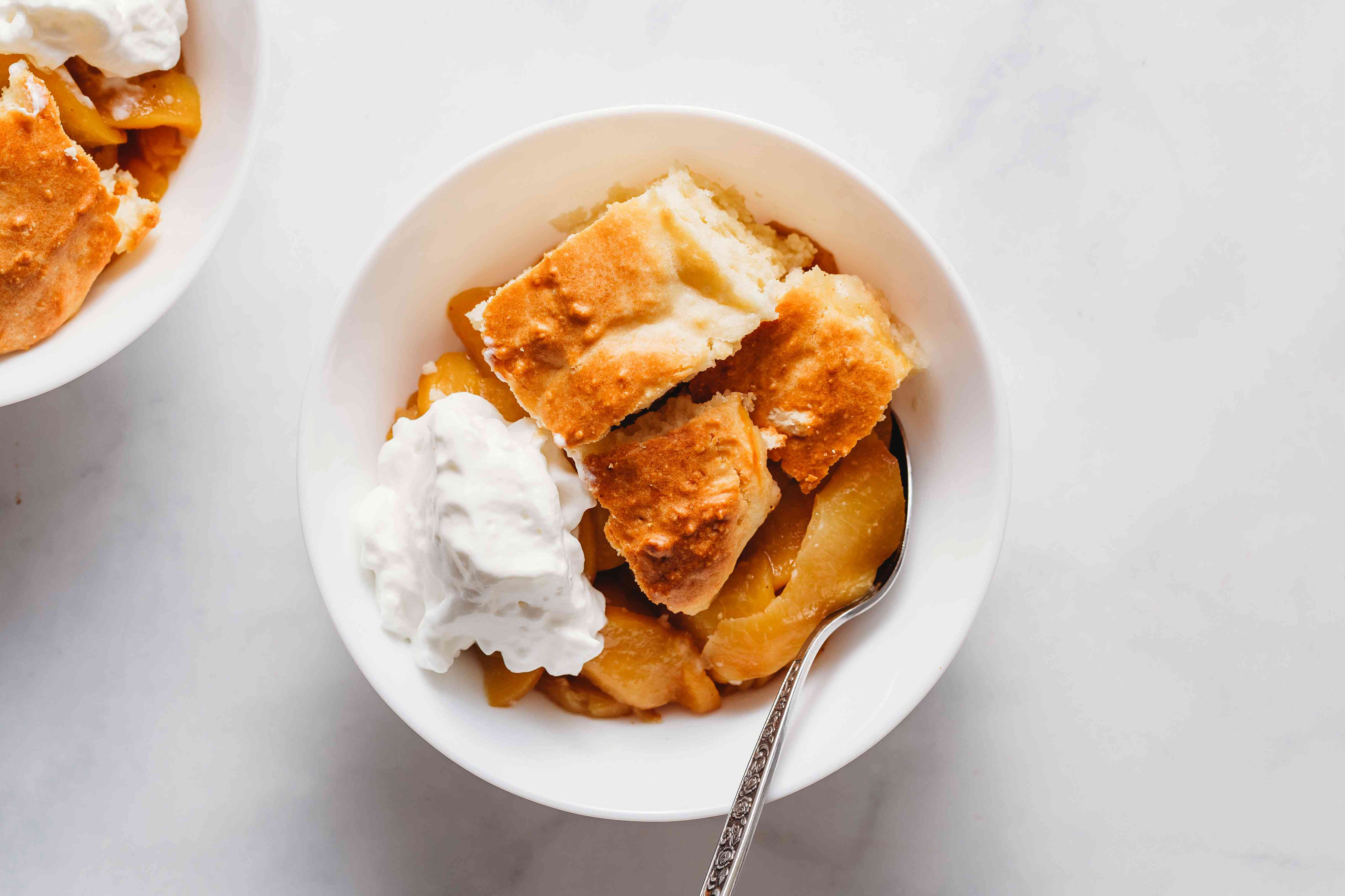 Fresh Peach Slump in a bowl served with whipped cream