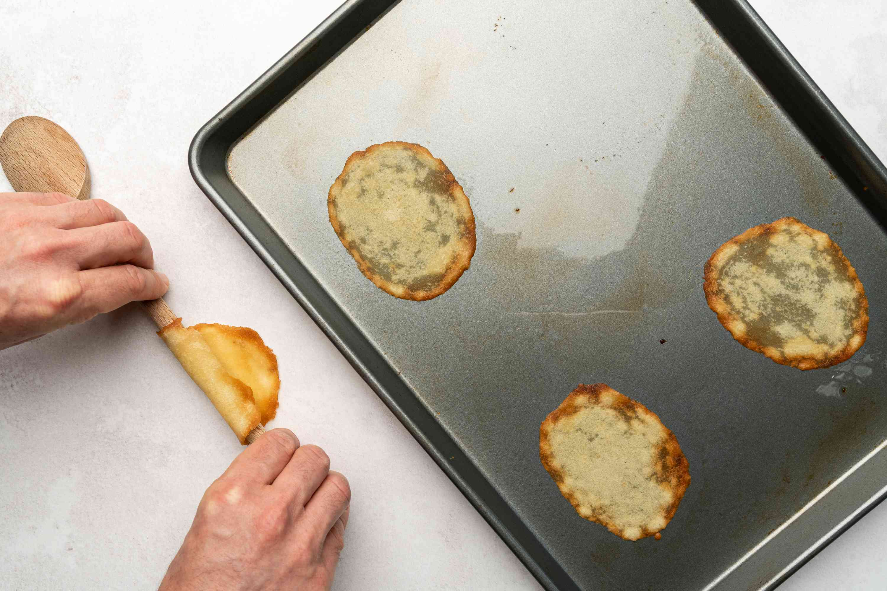 cookies rolled around the end of a wooden spoon, cookies on a baking sheet