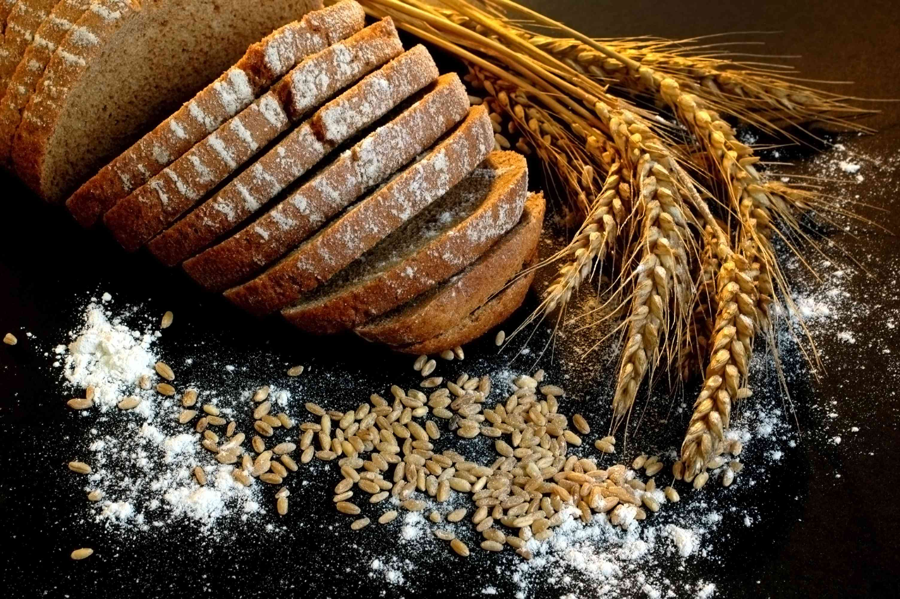 Close-Up Of Wheat And Brown Breads Over Black Background