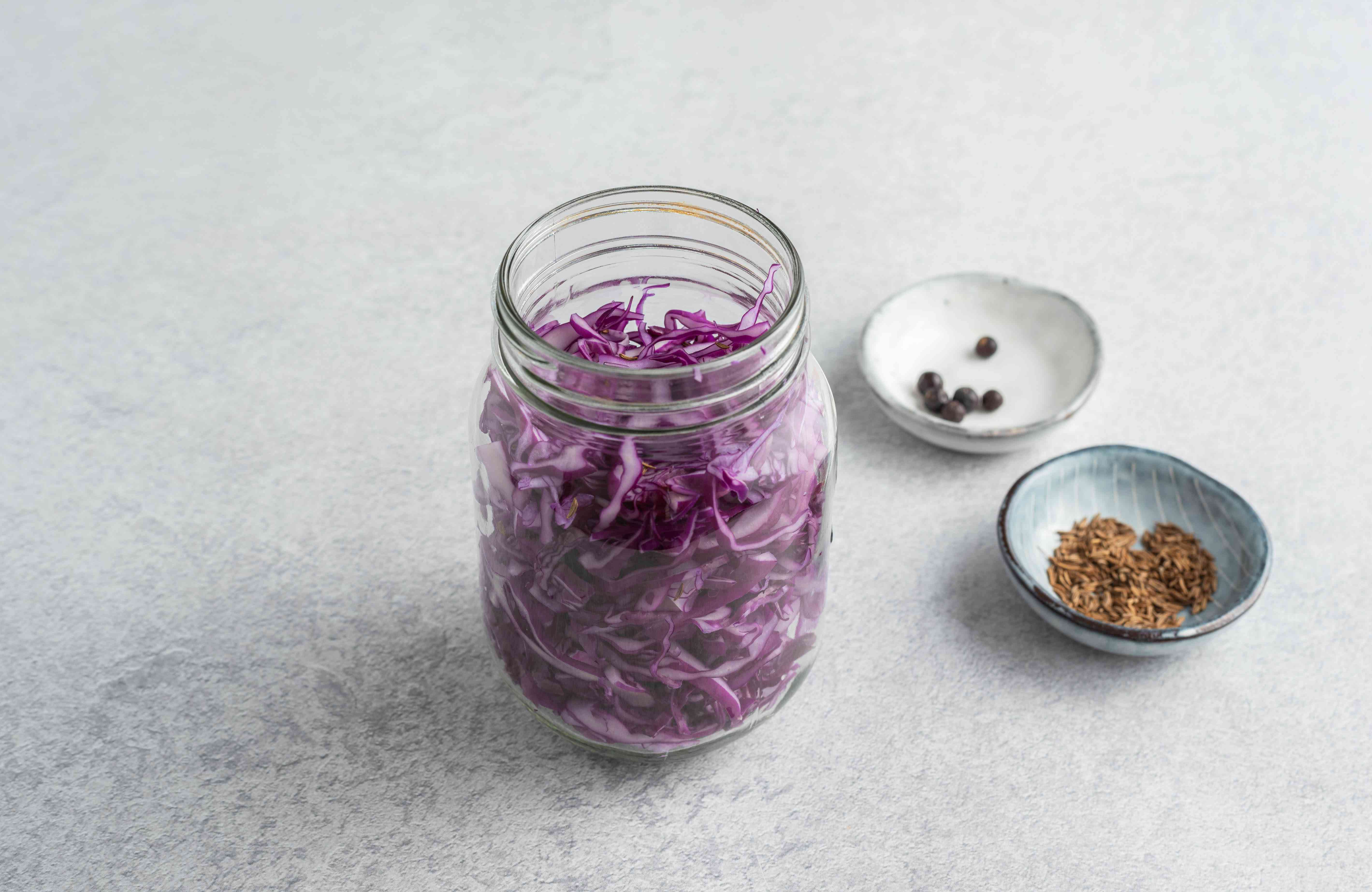 Sliced red cabbage in a jar; caraway seeds and juniper berries