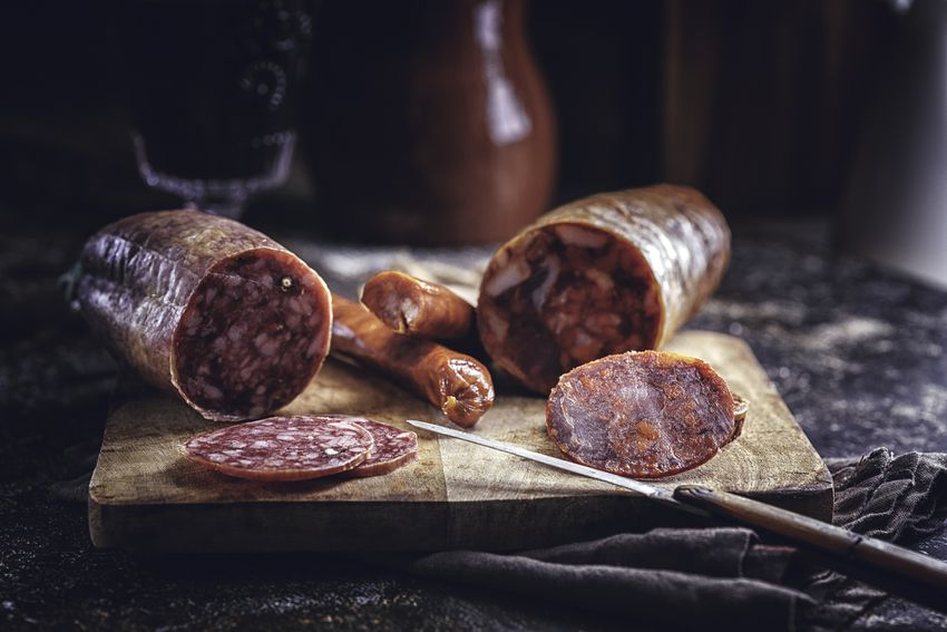 two dried sausages on a brown cutting board