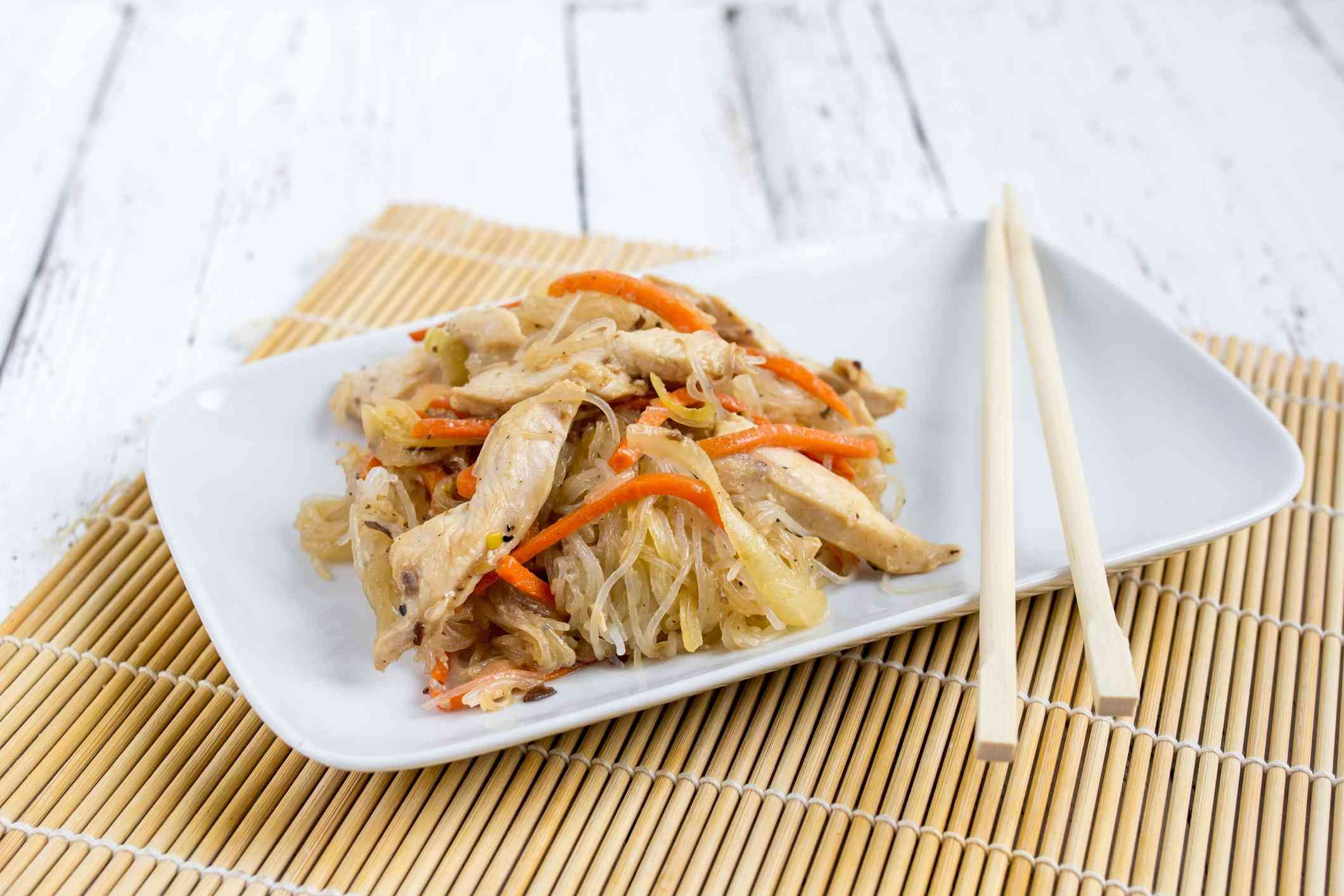 Chapchae (Stir-Fried Korean Noodles) on a white plate with chopsticks