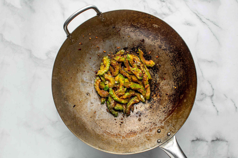Stir in a few drops sesame oil into the bitter melon in the wok