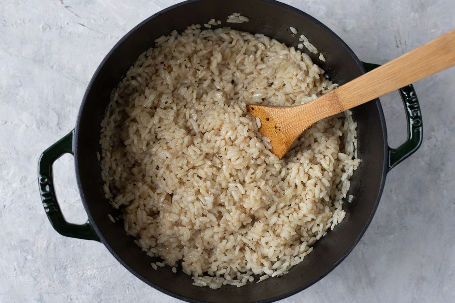 Risotto in a saucepan with a wooden spoon