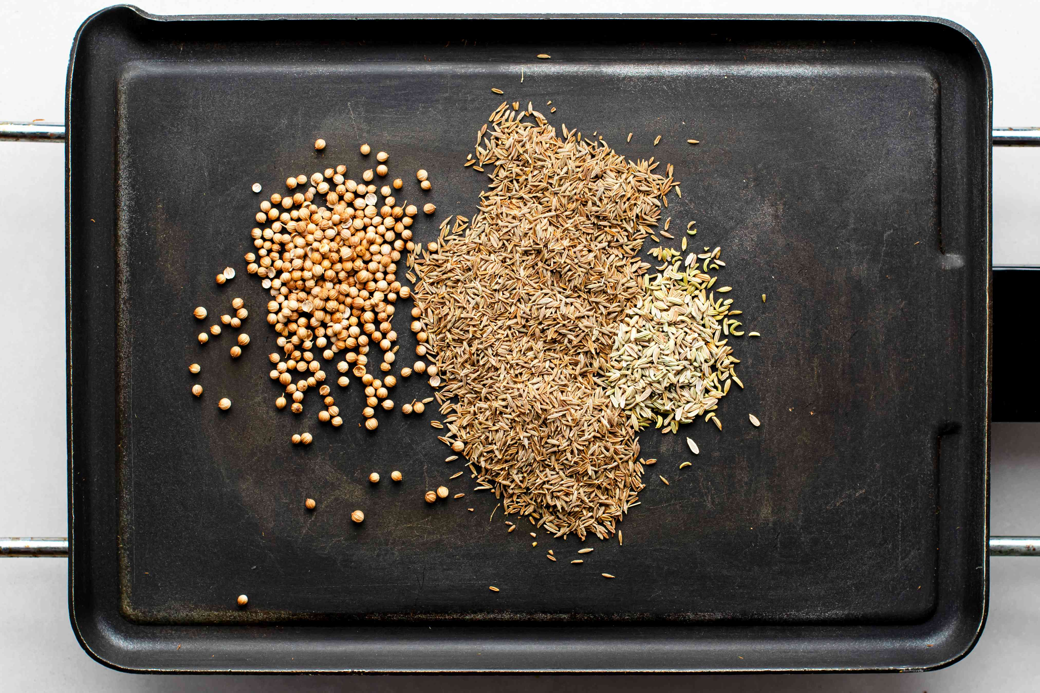 Cumin, coriander, and fennel seeds on a grill