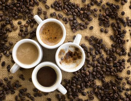 Assorted coffee drinks in cups on coffee beans background