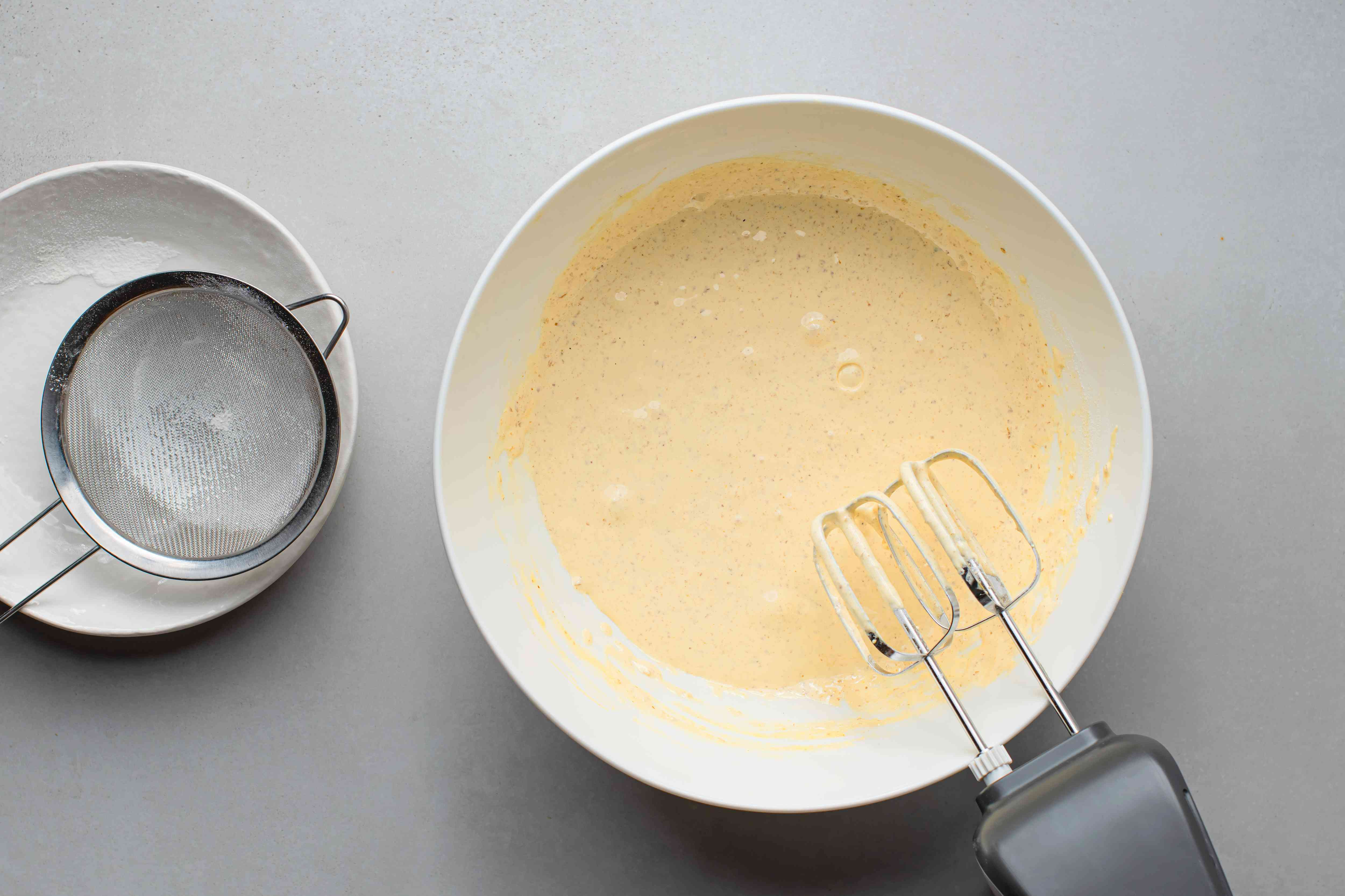 eggs, sugar, nuts, flour and baking powder mixed into a batter in a bowl