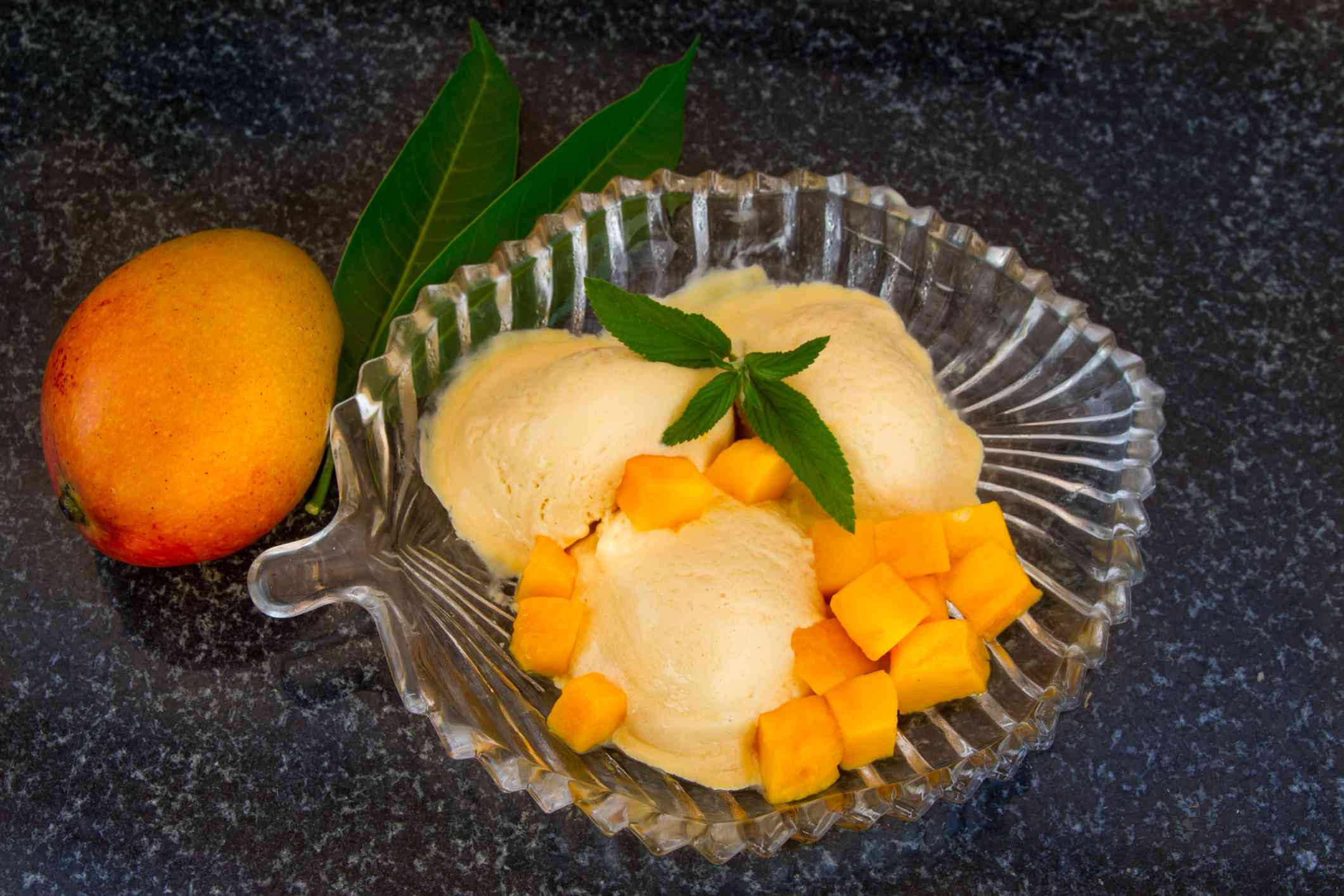 Mango ice cream with fresh mango slices with leaves mint on a glass plate