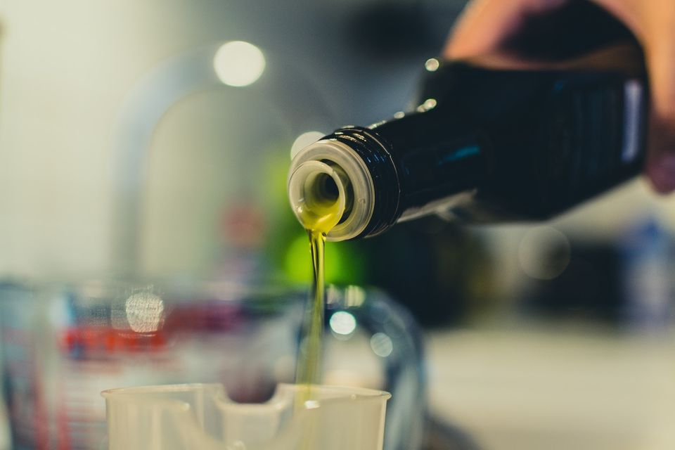 Cropped Image Of Woman Pouring Olive Oil In Jar
