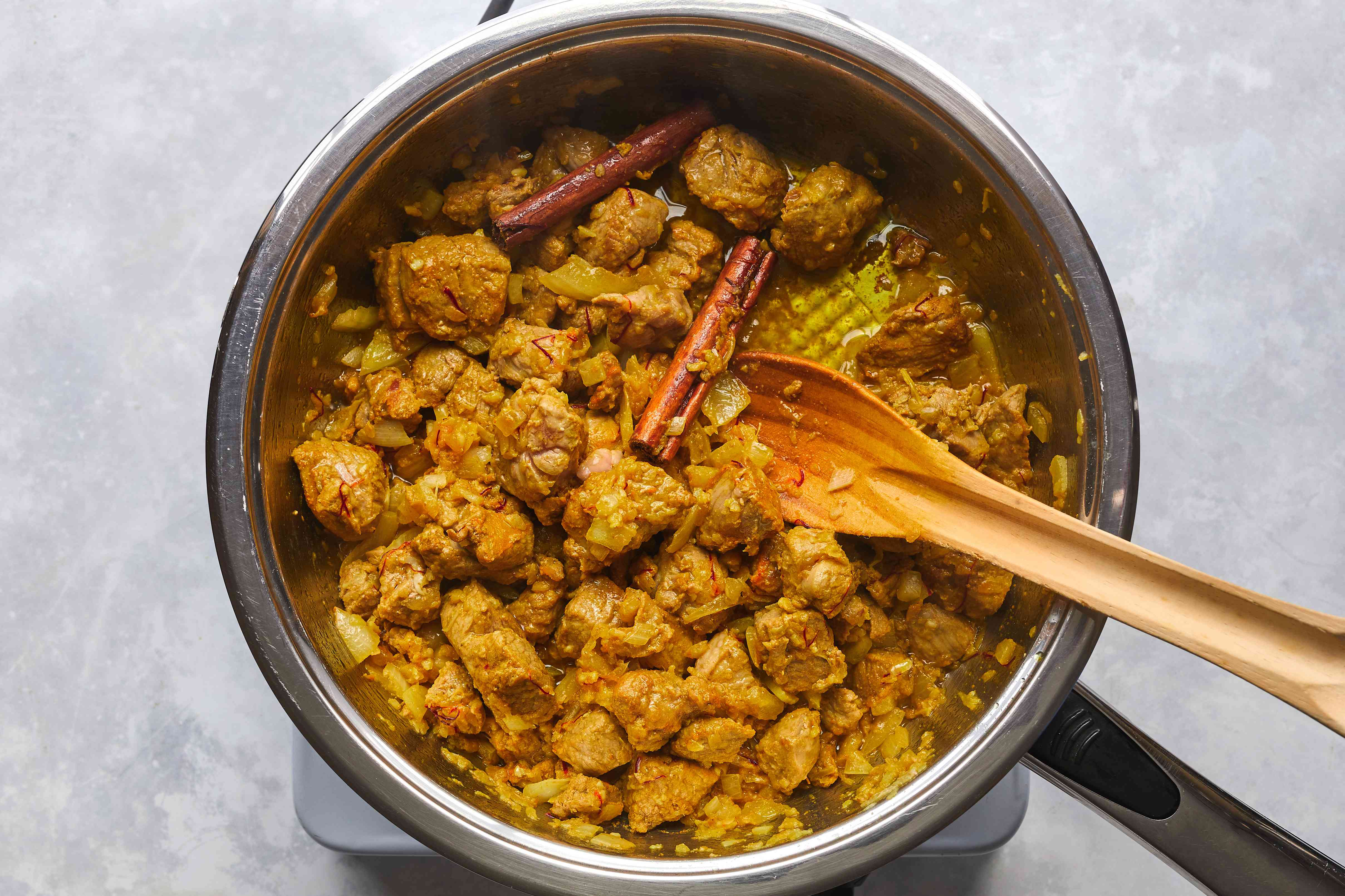 meat with onions, garlic, and spices cooking in a pot