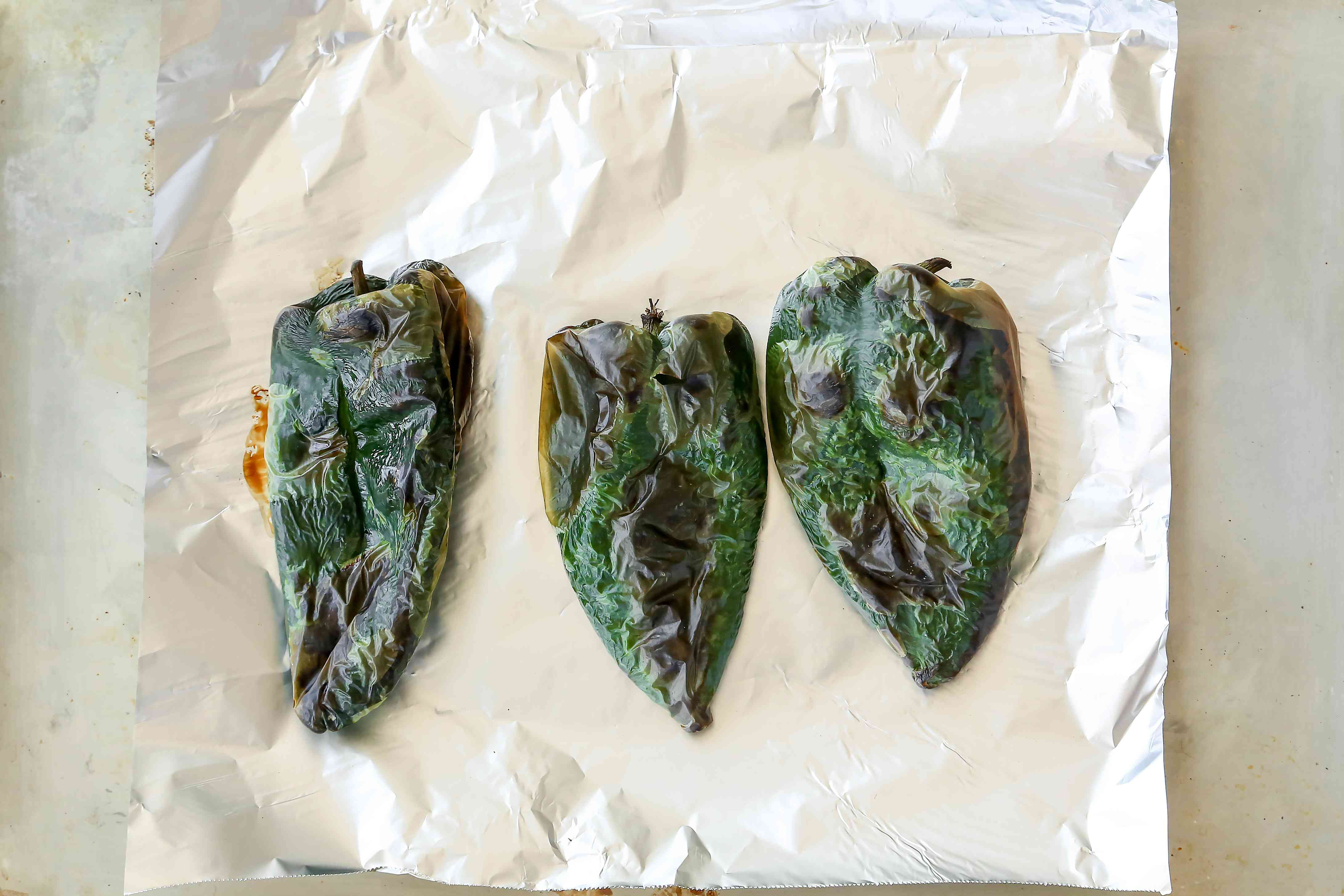 Roasted green chilies on aluminum foil