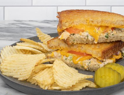 tuna melt sandwich on a plate with chips and pickles