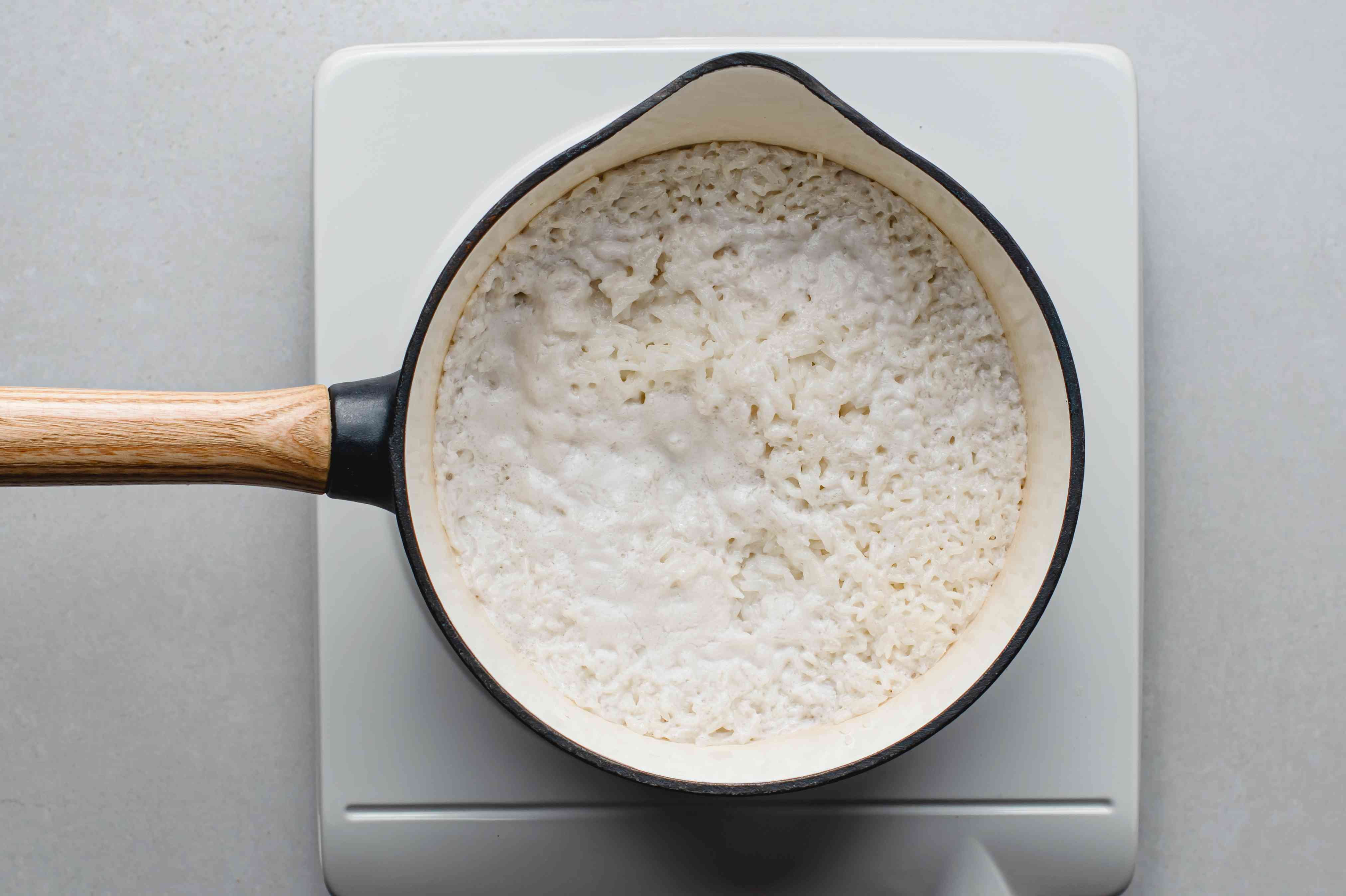 rice cooking with coconut milk in a saucepan