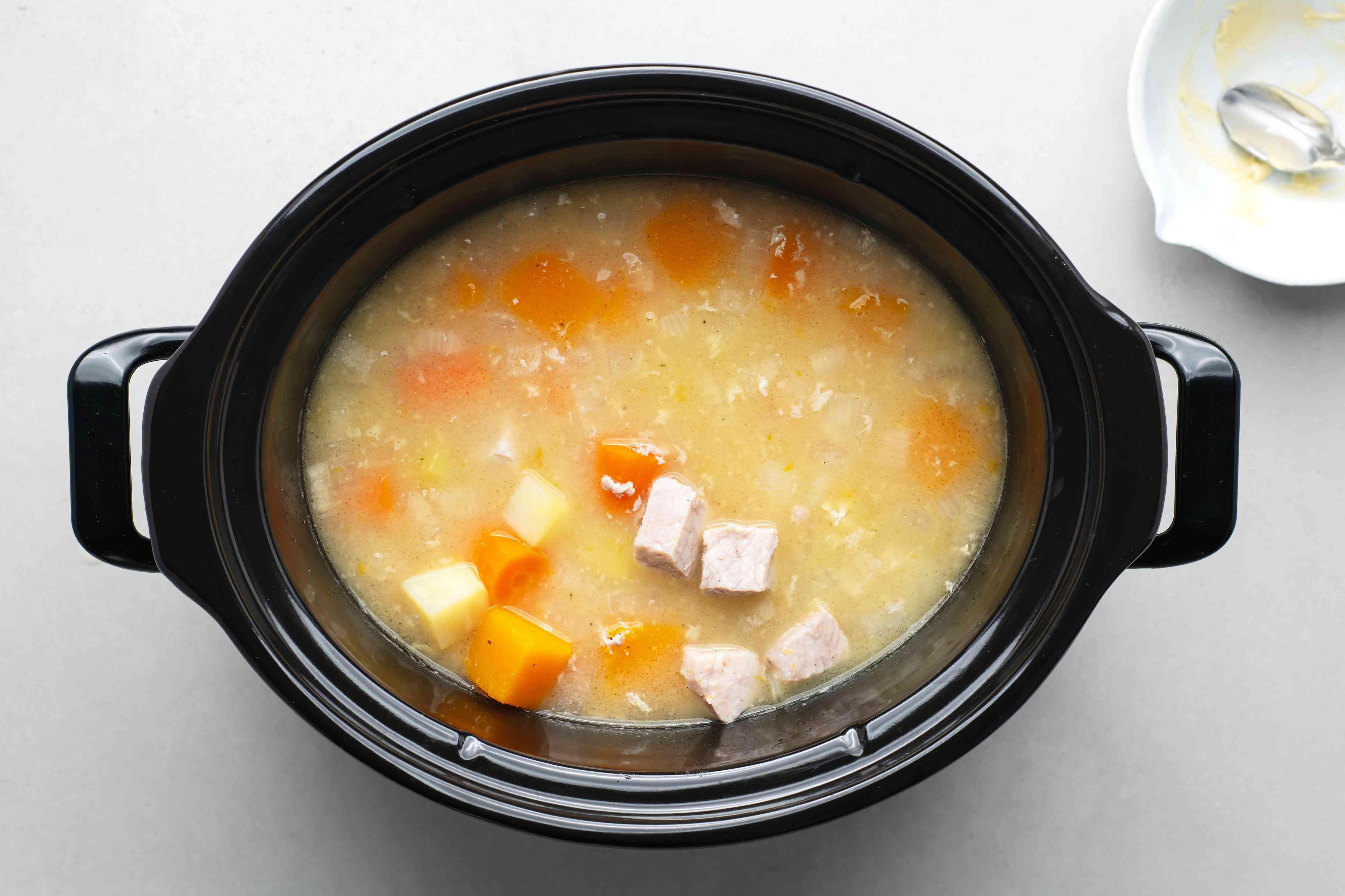 Pork stew cooking in a crock pot, flour mixture added