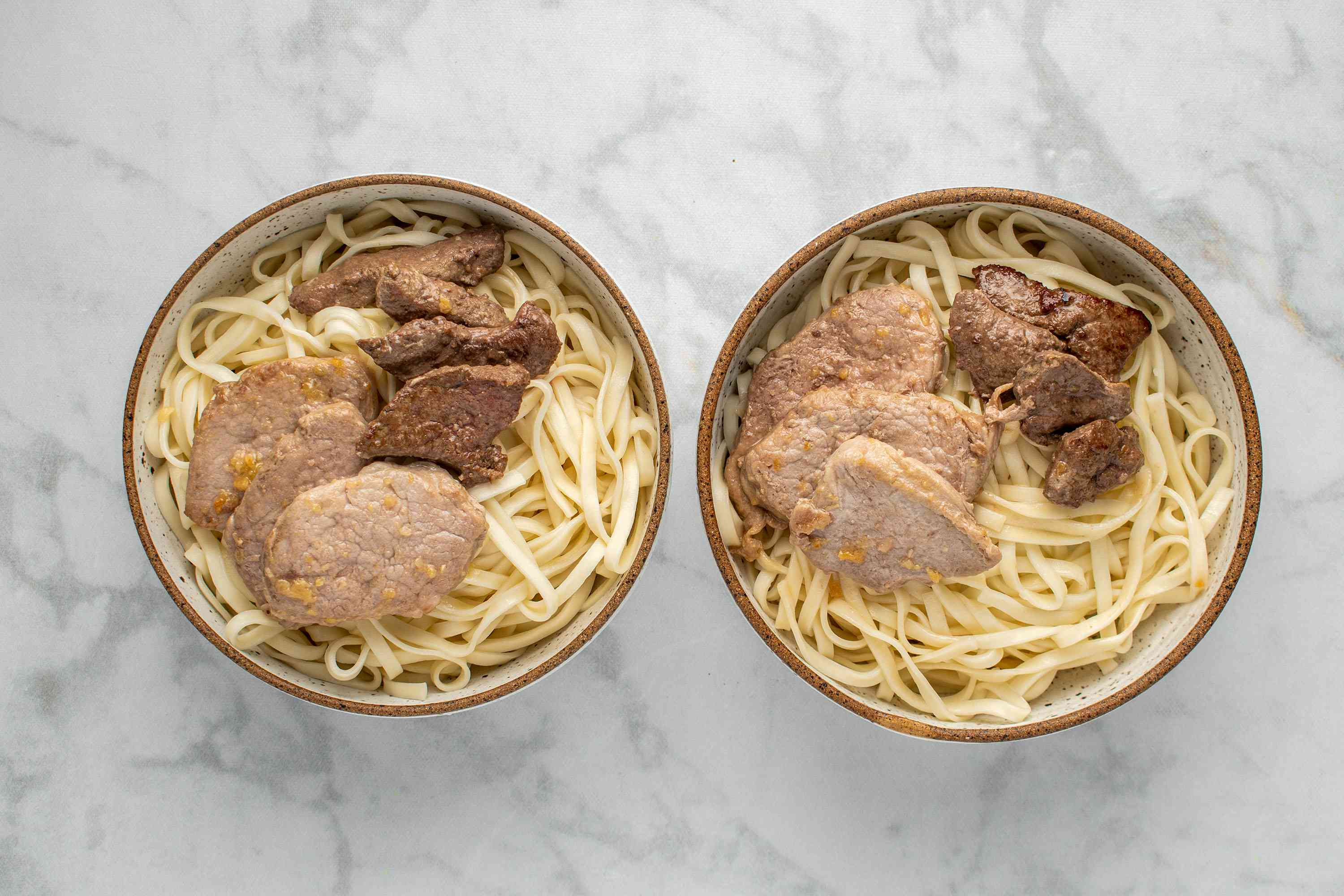 Divide the sauteed meat between the two bowls with noodles