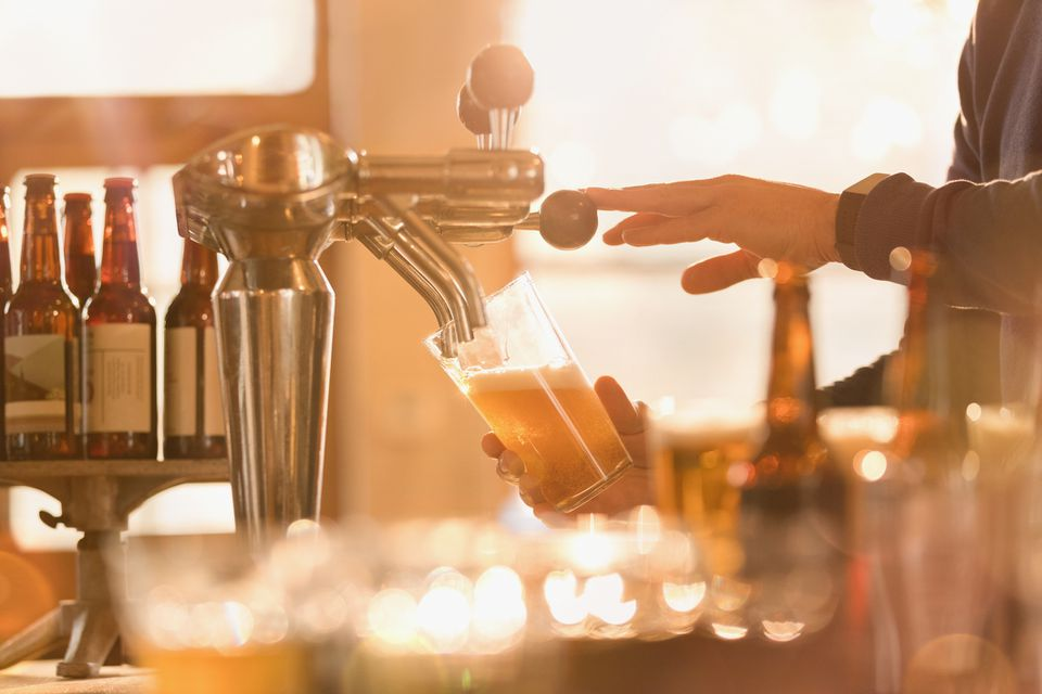 bartender serving light beer from a tap