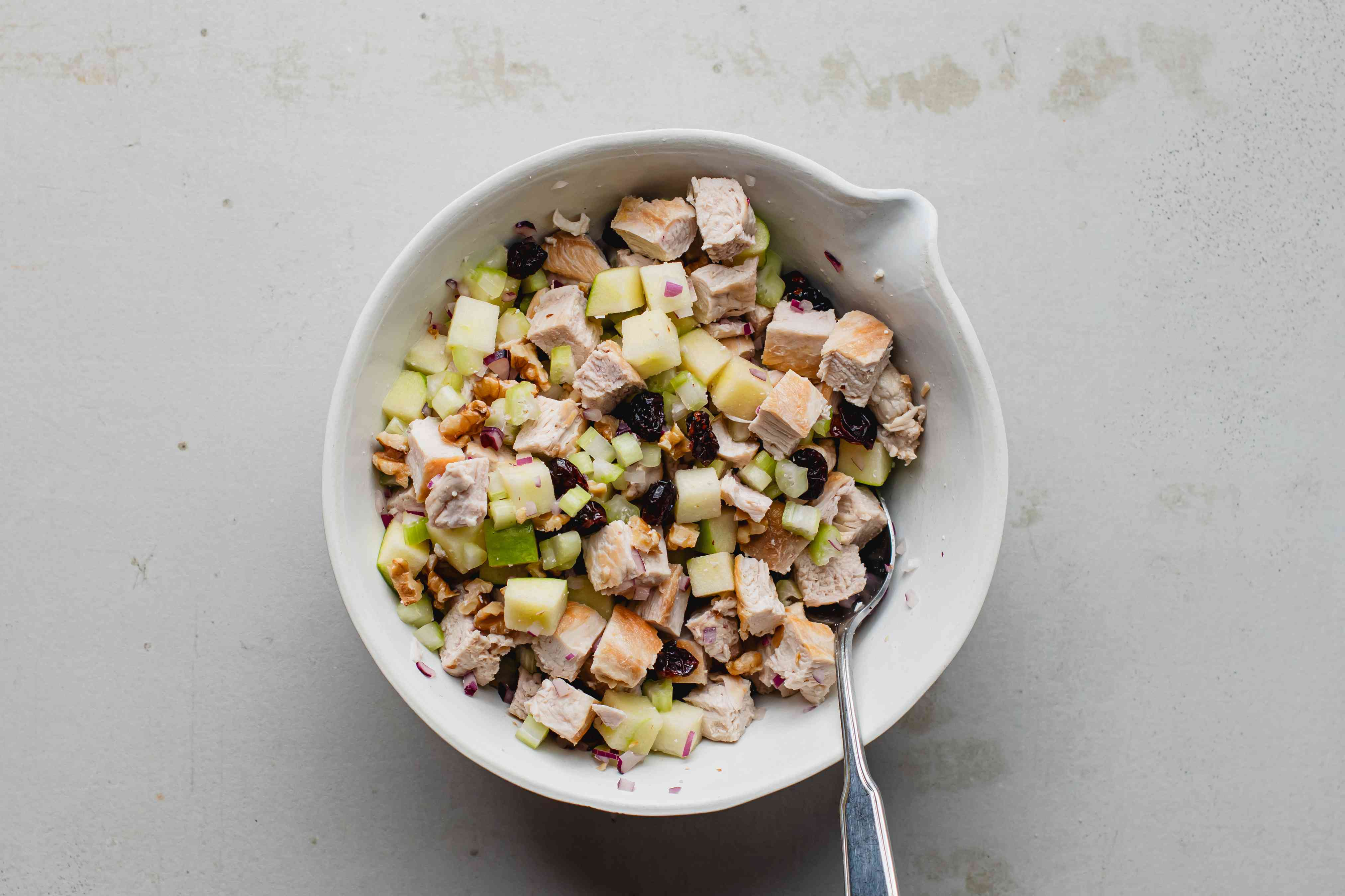 Diced chicken, apples, cranberries, walnuts, and celery in a bowl
