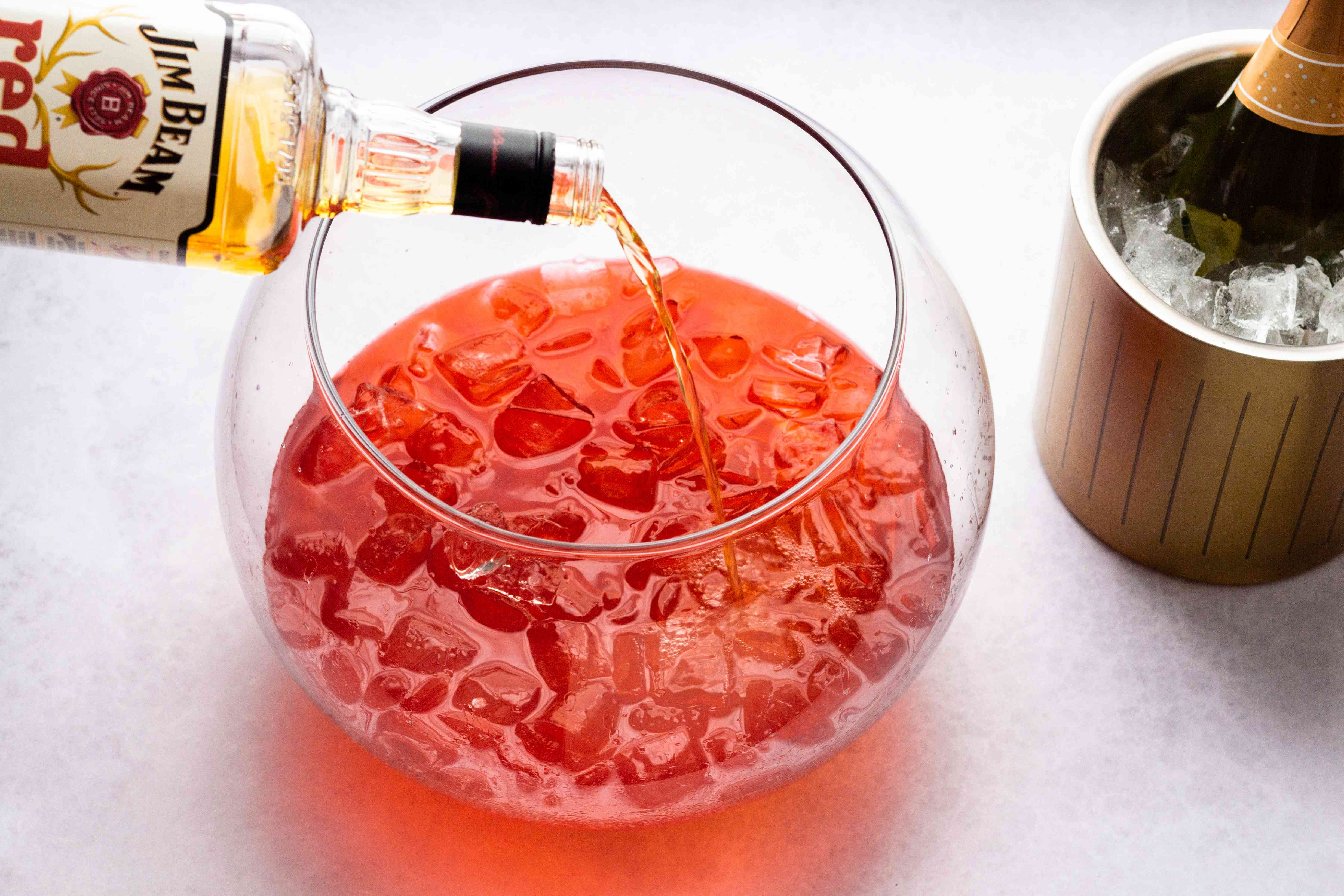 Pour the cherry whiskey, strawberry liqueur, and passion fruit into a punch bowl with plenty of ice