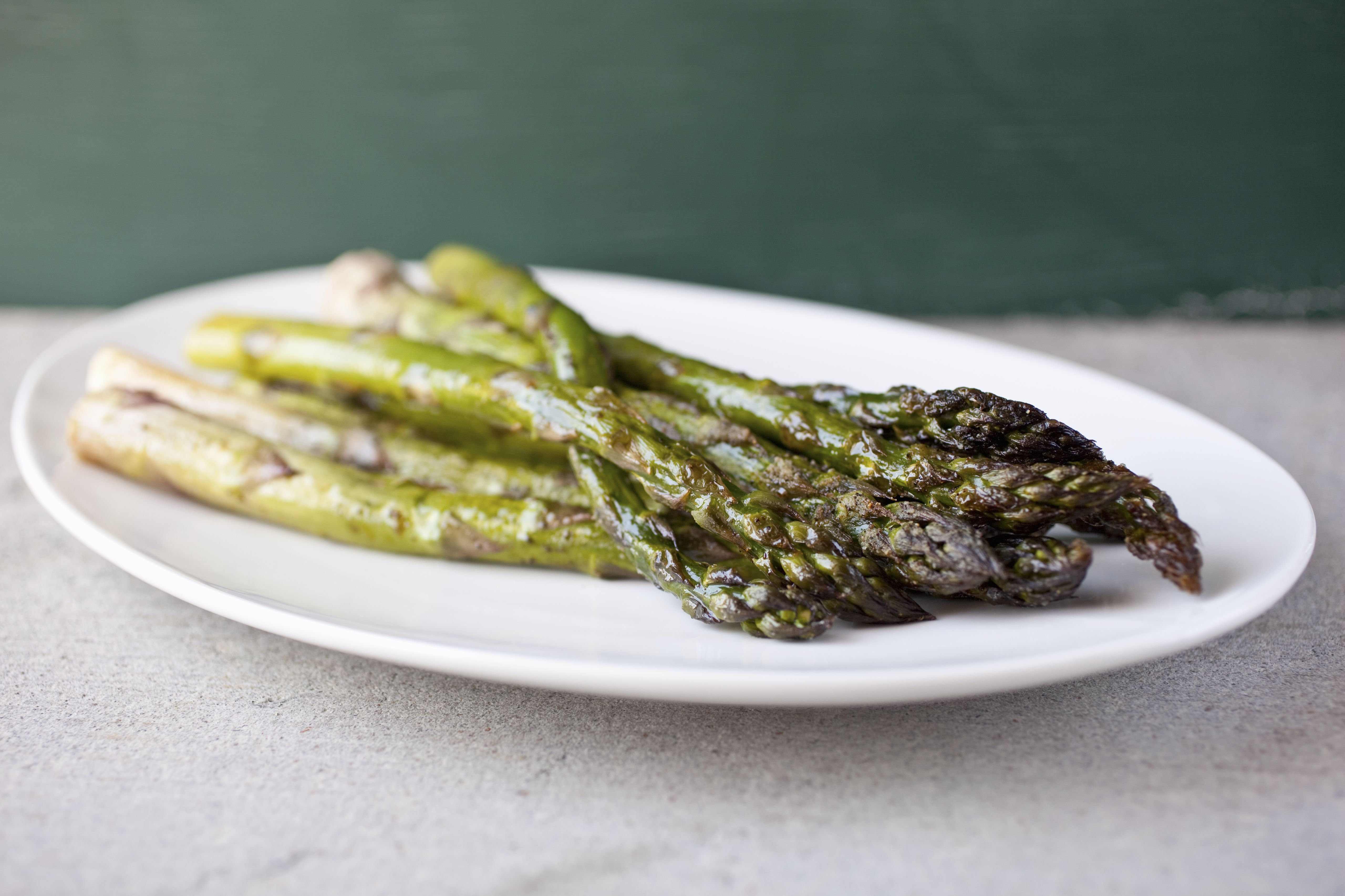Roasted asparagus on white platter, close-up