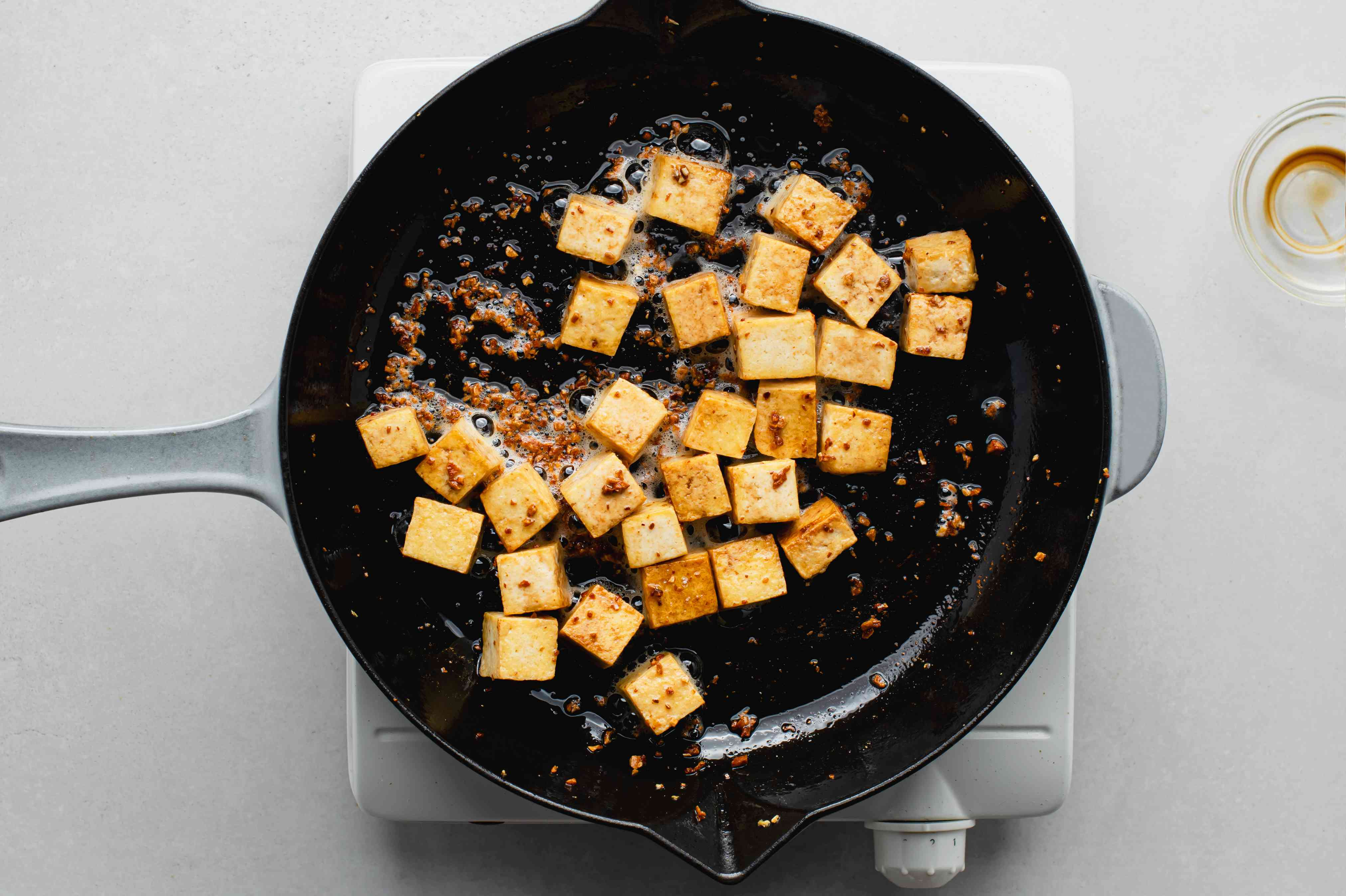 tofu and garlic in a skillet with soy sauce